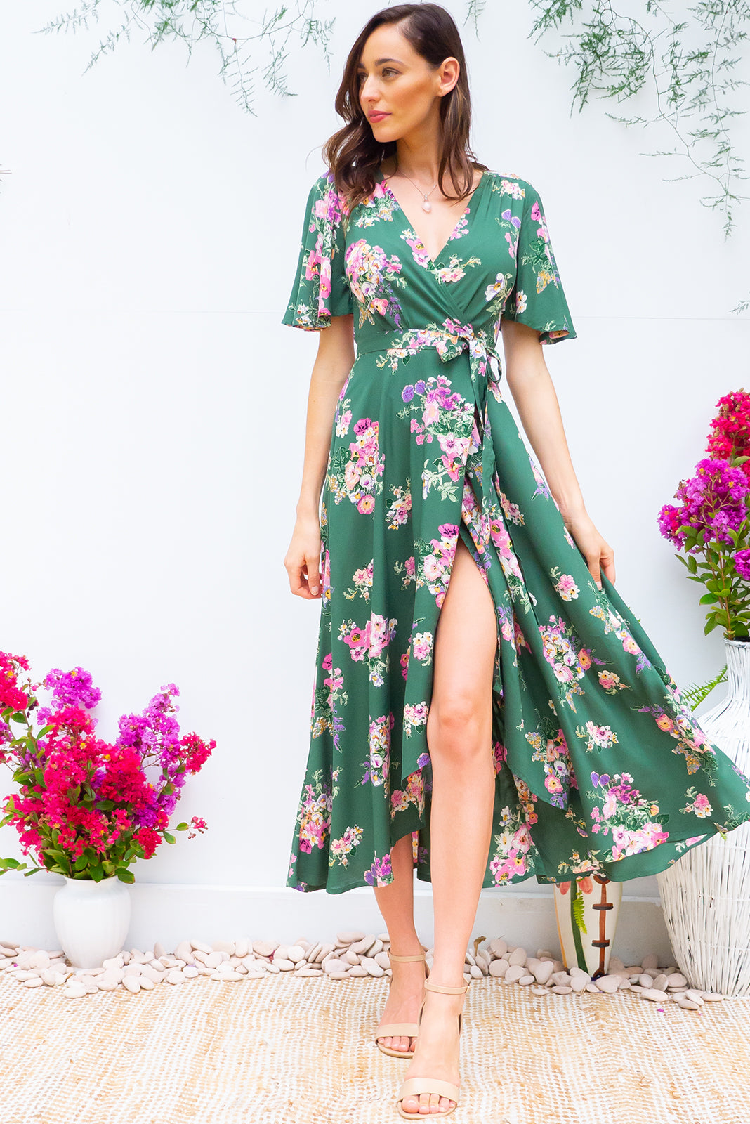 Petal Zinnia Green Maxi Wrap Dress dress features a flattering wrap around waist, petal sleeves, and a shorter at the front hemline and comes in a soft forest green with a delicate bohemian floral  bouquet print on rayon