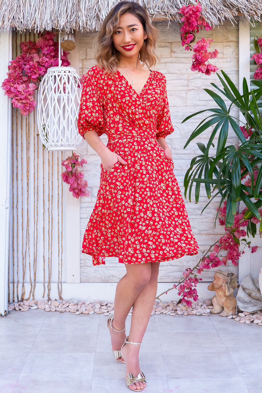 The Poppi Crimson and Clover Wrap Dress features flattering adjustable wrap design, elasticated waist band at the back, puff sleeves, side pockets and 100% rayon in red base with beige and green floral print.