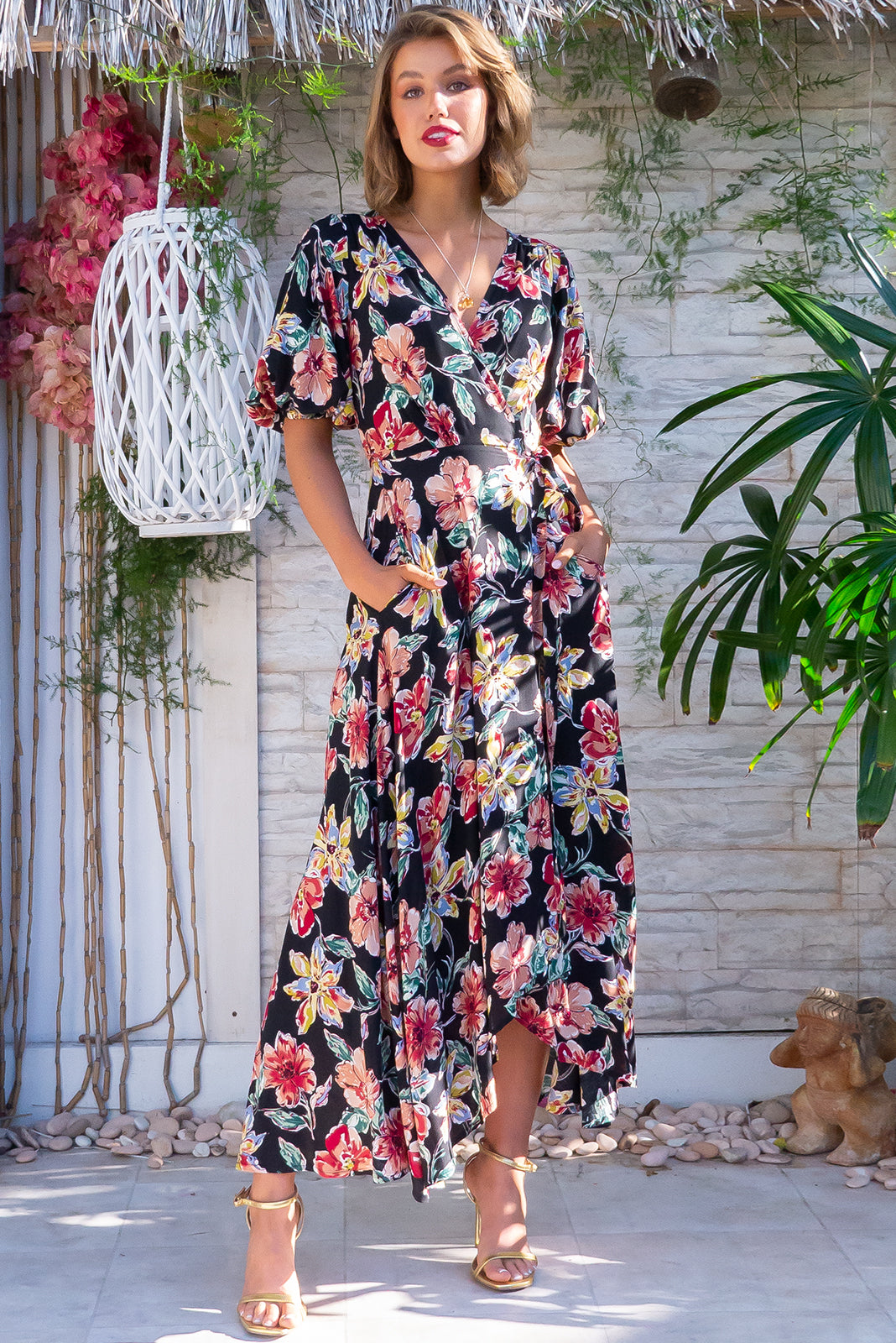 The Posy Blooming Black Maxi Wrap Dress is flattering adjustable wrap design featuring puff sleeves, scooped hemline, elasticated waist band at the back, side pockets and 100% rayon in black base with large retro floral print.