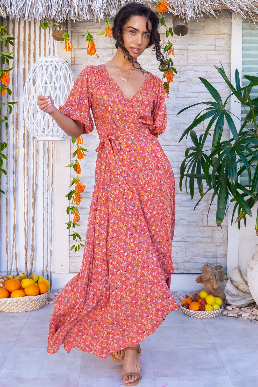The Posy Terracotta Maxi Wrap Dress features puff sleeves, scooped hemline, shorter at front, flattering adjustable wrap design, elasticated waist band at the back, side pockets and woven 100% rayon in terracotta base with floral pattern.