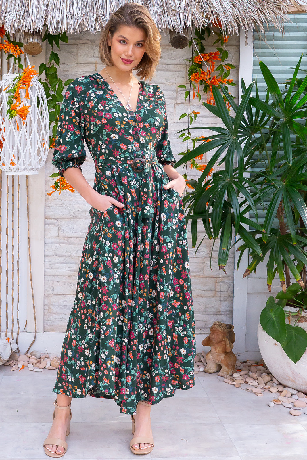 Primrose Autumn Green Dress features functional buttons from bust to waist, 3/4 sleeve with shirring cuffs, side pockets and woven 100% rayon in Green base with cream, pink and orange floral pattern.