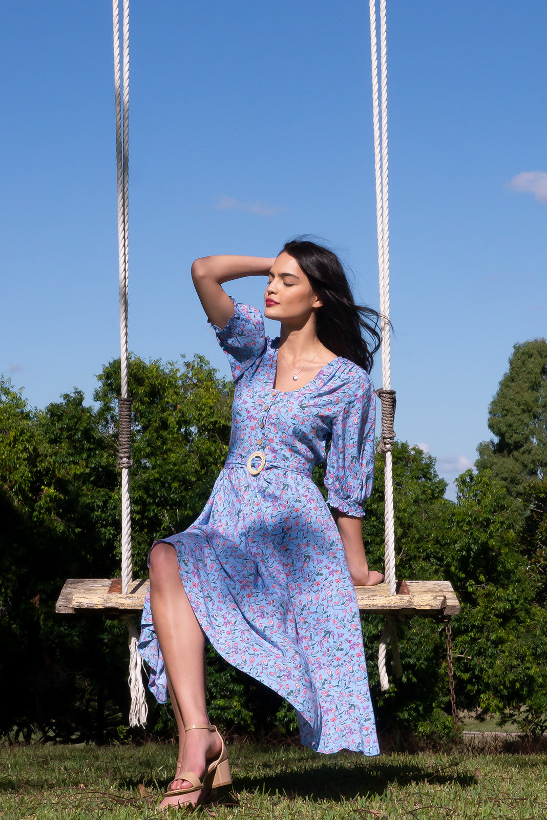 The Primrose Cornflower Blue Dress features functional buttons from bust to waist, elasticated back waistband, 3/4 sleeve with shirring cuffs, side pockets, woven 100% rayon in sky blue base with pink floral vine print and coming matching belt to cinch waist.