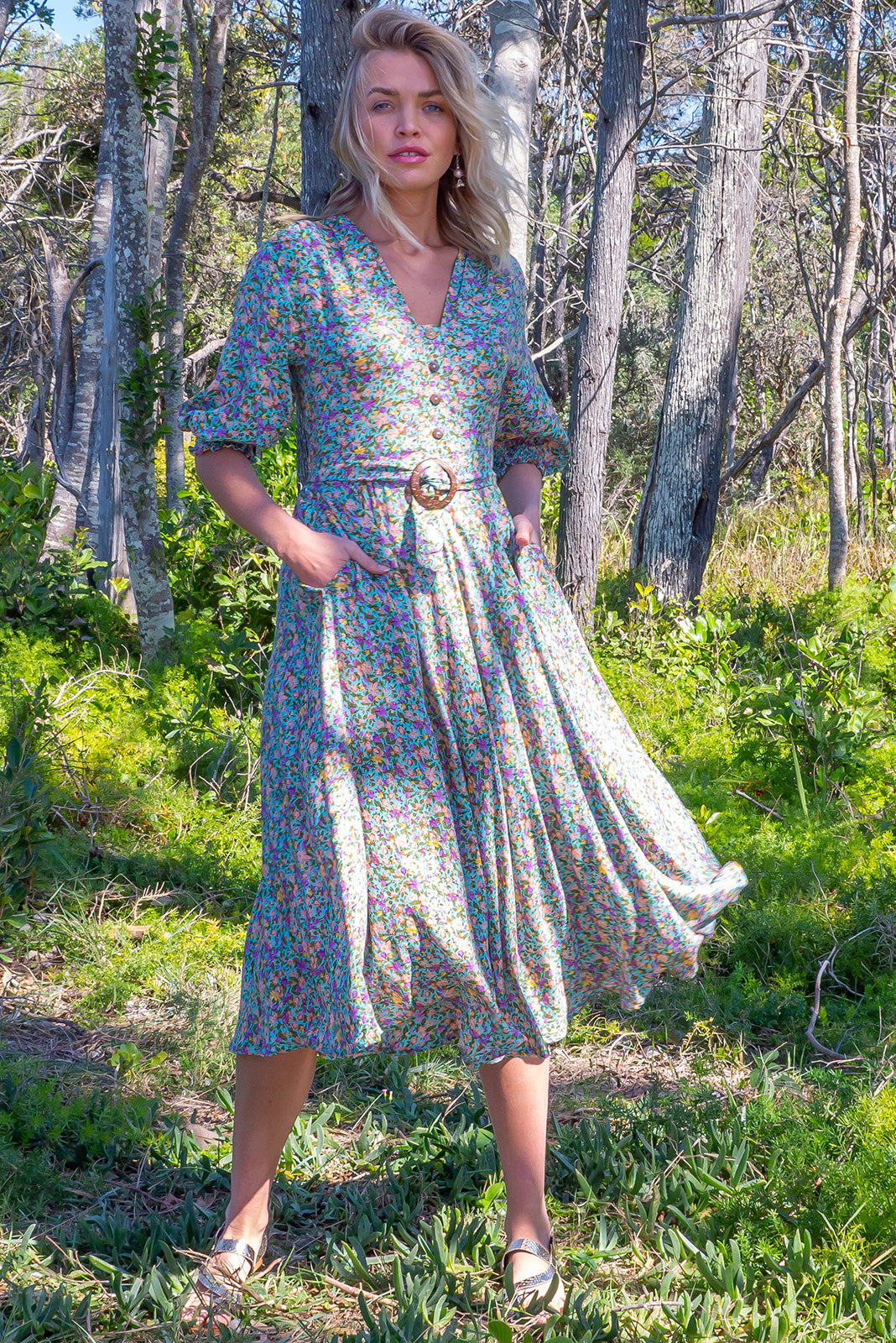 The Primrose Carolina Mint Dress is a V neckline midi dress featuring elasticated back waistband, 3/4 sleeve with shirring cuffs, side pockets, slightly curved hemline and 100% viscose in minty green blue with green, purple & beige floral print.