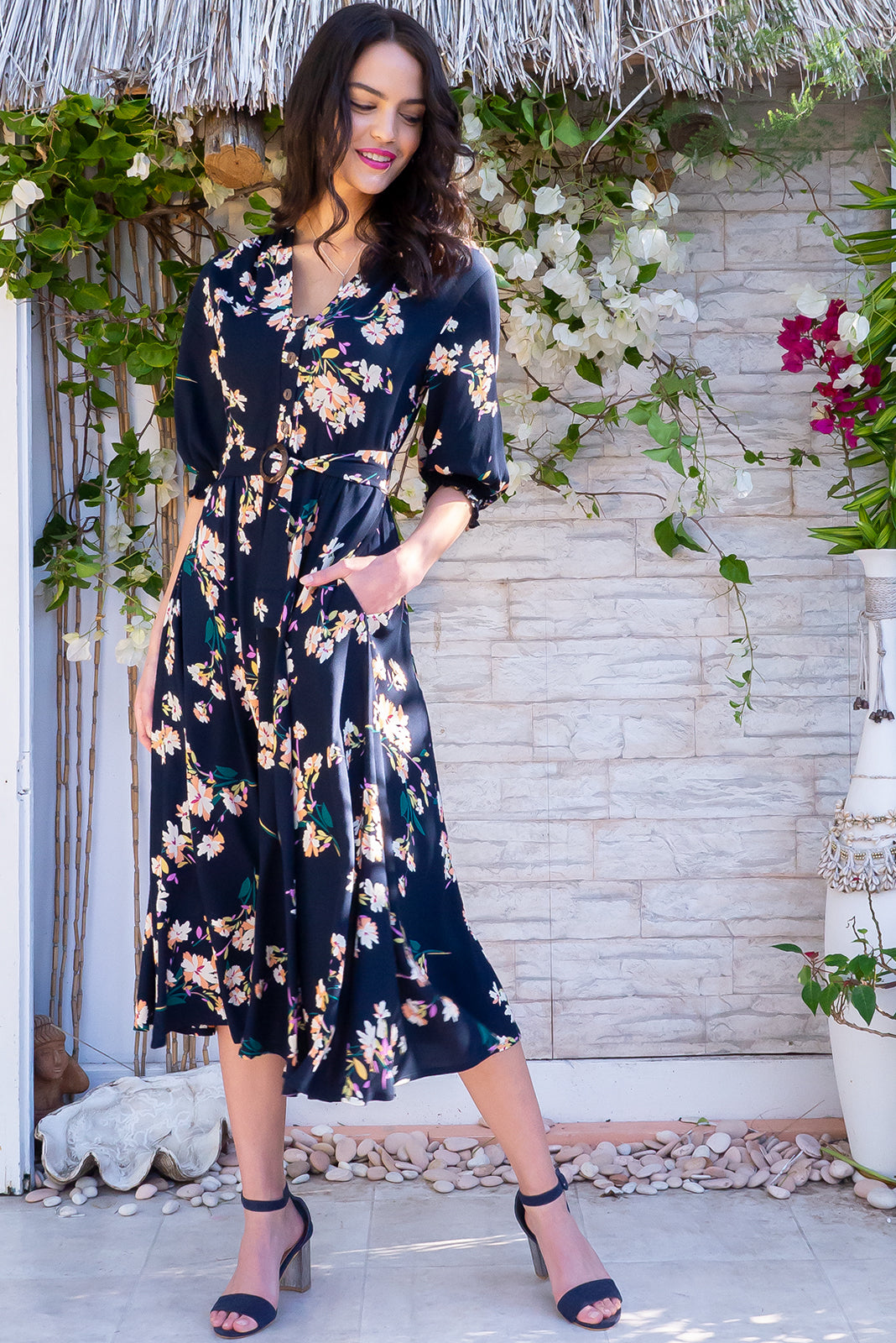 Primrose Inky romance Dress is a V neckline midi dress featuring Elasticated back waistband, 3/4 sleeve with shirring cuffs, Side pockets and woven 100% rayon in inky navy base with a modern peach, yellow, purple and green floral pattern.