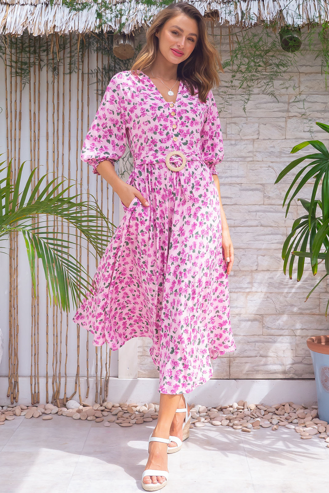 Primrose In he Pink Dress features V neckline, functional buttons from bust to waist, elasticated back waistband, 3/4 sleeve with shirring cuffs, side pockets and 100% rayon in pink base with mauve floral print.