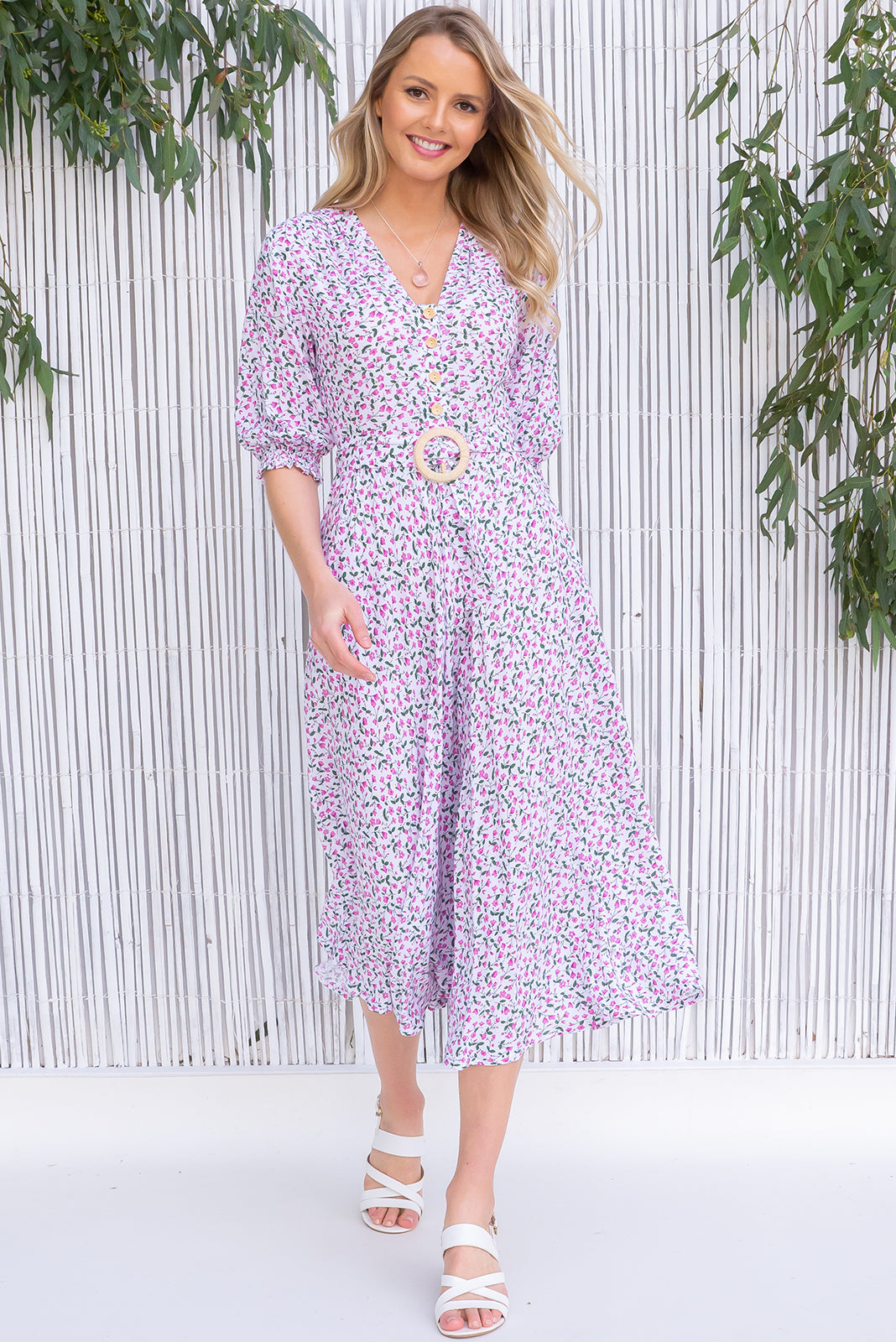 Primrose Portia Pink Dress features functional buttons from bust to waist, 3/4 sleeve with shirring cuffs, side pockets and woven 100% rayon in white base with mini pink and green floral pattern.