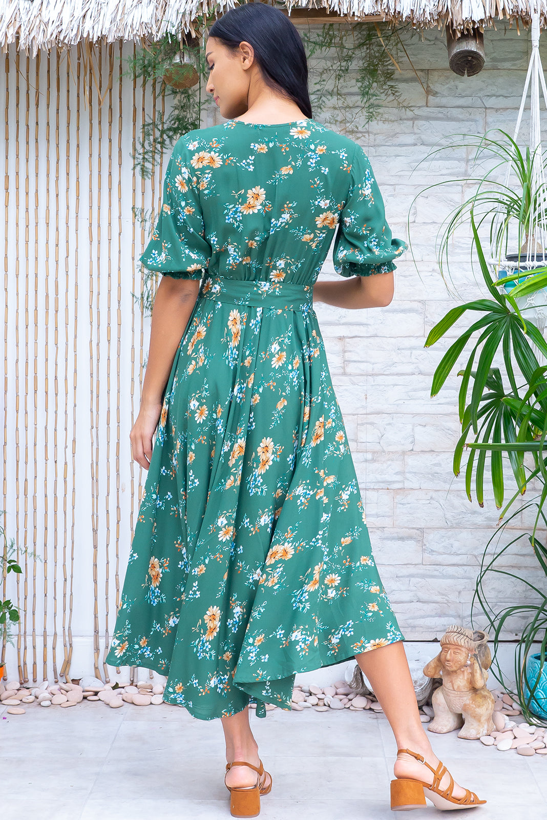 The Primrose Springtime Green Dress is a retro V neckline midi dress featuring functional buttons from bust to waist, elasticated back waistband, 3/4 sleeve with shirring cuffs, side pockets, slightly curved hemline and 100% rayon in green base with classic floral print.
