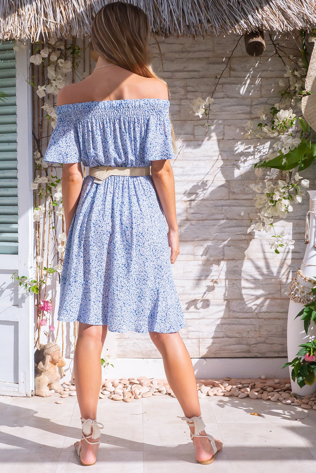Roxie Blue Daze Mini Dress, summer bohemian style, 100% viscose, has soft elastic and ruching to gently hold the dress across the shoulders, side pockets, elasticated waist, deep sky blue base with a small white floral print.