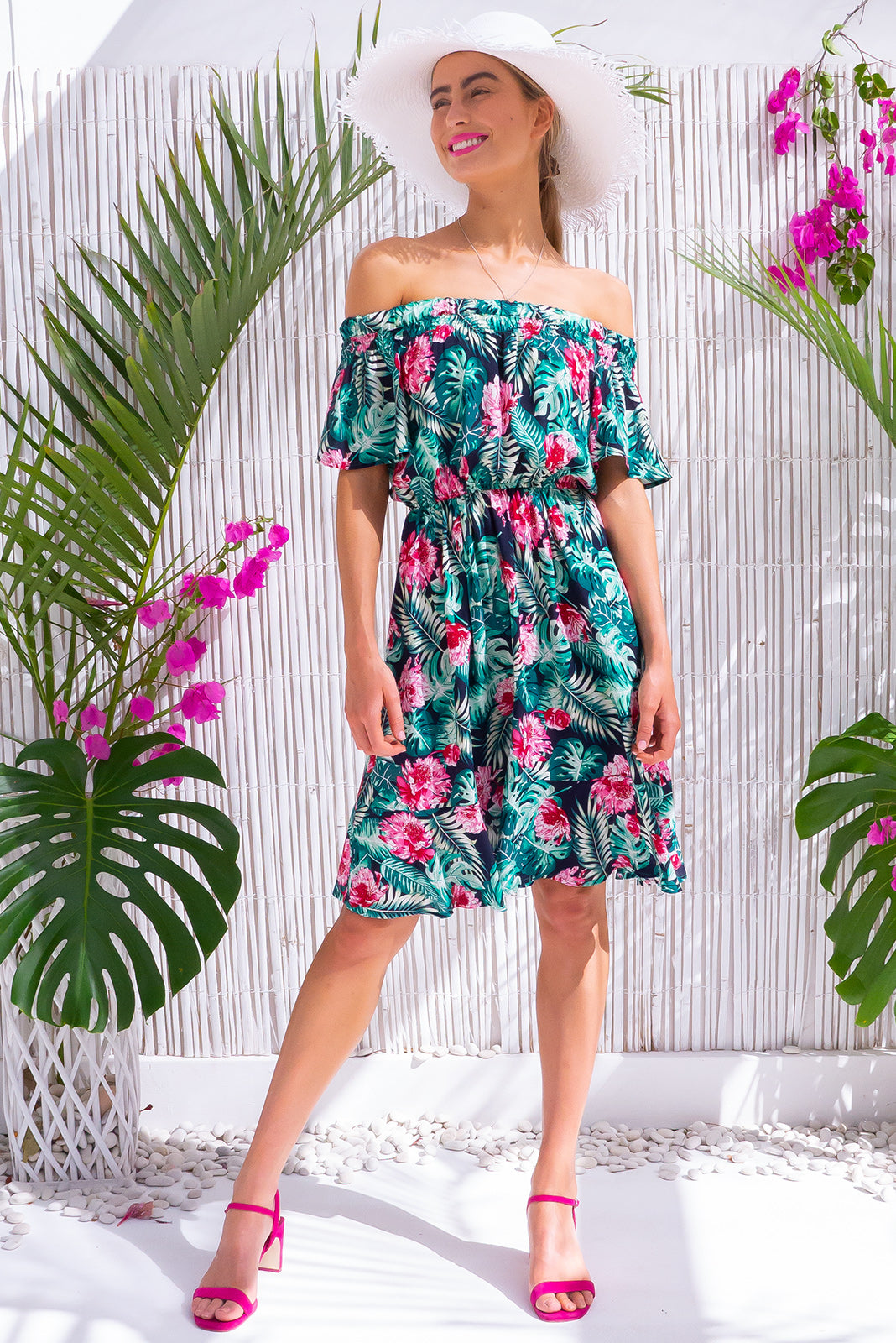 Roxie Night Palms Mini Dress, bohemian summer style, 100% viscose, soft elastic ruching gently holds dress across shoulders, side pockets, elastic waist, navy base with fuchsia, soft pink, teal and soft green floral and palm print.