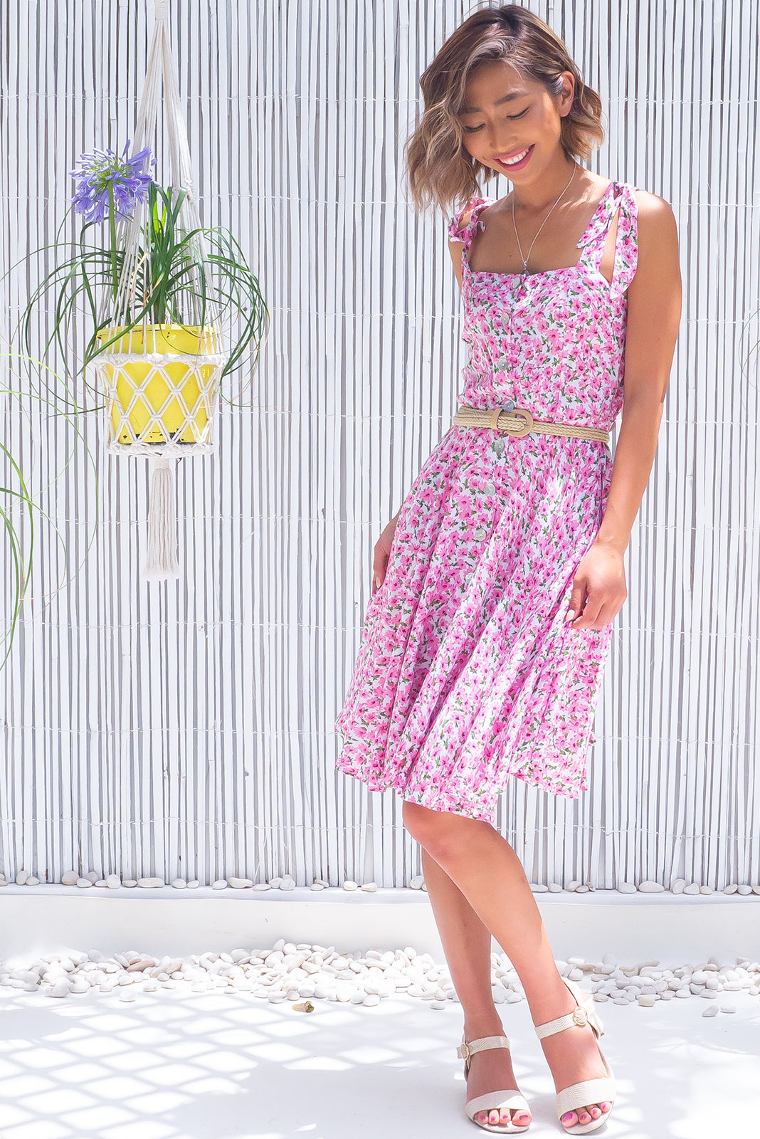 The Ruby Tuesday Fresh Pink Dress features straight neckline, tie up shoulder straps, functional button front, side pockets, elasticated waist back, full-circle hemline and 100% viscose in white base with pink flower print and this comes with a woven belt.