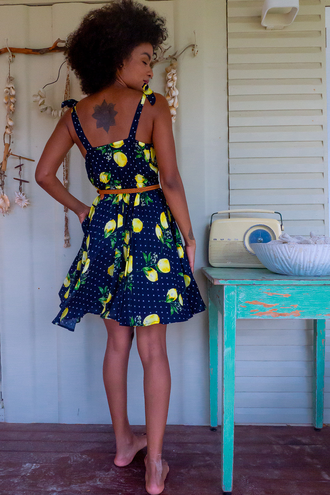 The Ruby Tuesday Limoncello Ink Dress is a retro mini dress featuring straight neckline, tie up shoulder straps, functional button front, side pockets, elasticated waist back , 100% viscose in inky base with cute lemons and polkadot print and woven belt included.