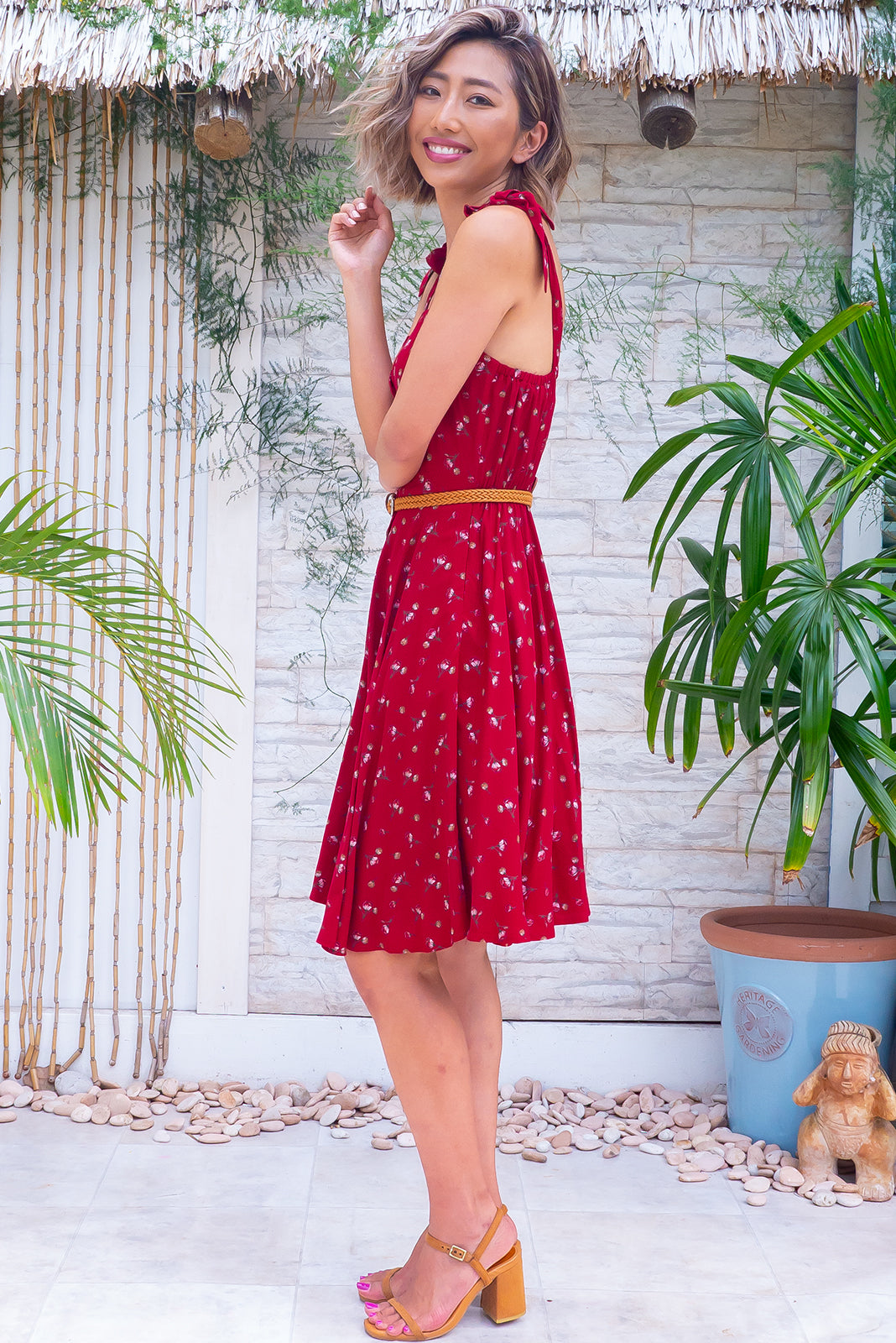 The Ruby Tuesday Real Red Dress is a retro mini dress featuring straight neckline, tie up shoulder straps, functional button front, side pockets, elasticated waist back, woven belt included, full-circle hemline and 100% viscose in deep red base with small floral print.