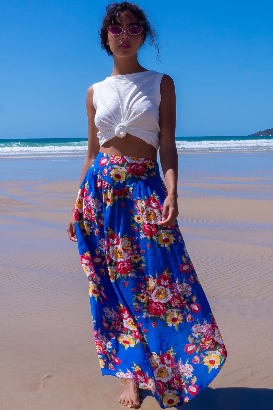 The Sails Culebra Cotton Blue Maxi Skirt has scooped hemline featuring shorter at sides, V-shaped panelled waist band, elasticated back of waist, side pocket and 65% cotton, 35% rayon  in bold cobalt blue base with large summer floral print.