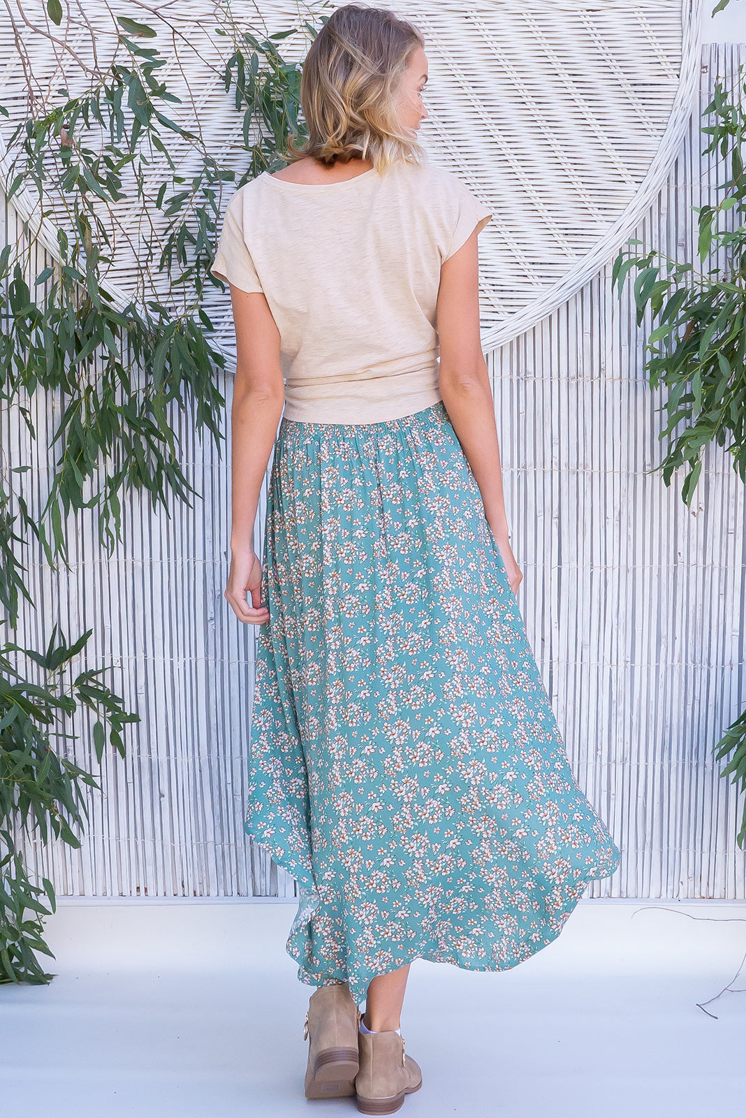 Sails Sage Scatter Maxi Skirt features scooped hemline shorter at sides, V-shaped panelled waist band, shirred back waist, functional side pockets, woven 100% rayon in soft green base with dainty floral print.
