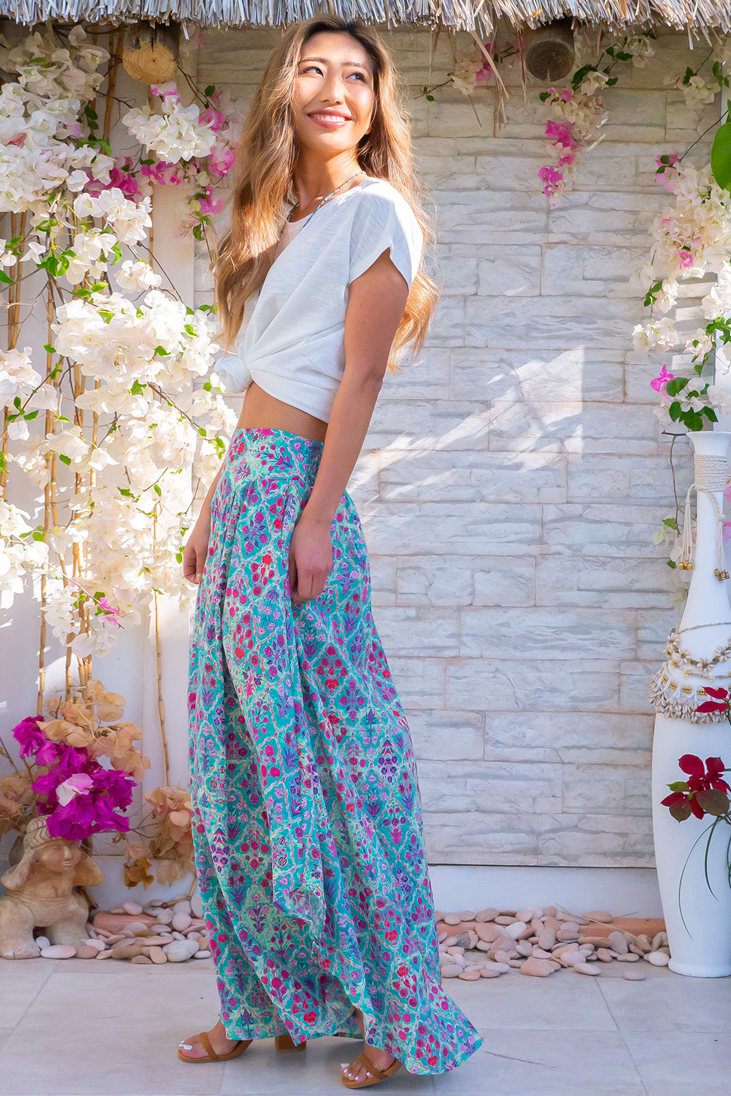 Sails Cadiz Cotton Teal Maxi Skirt, bohemian summers style, 65% cotton, 35% rayon, scooped hemline shorter at sides, v shaped panelled waist band, elasticated back of waist, side pockets, blue/green base with medium bright pink, purple, yellow and orange geometric print.