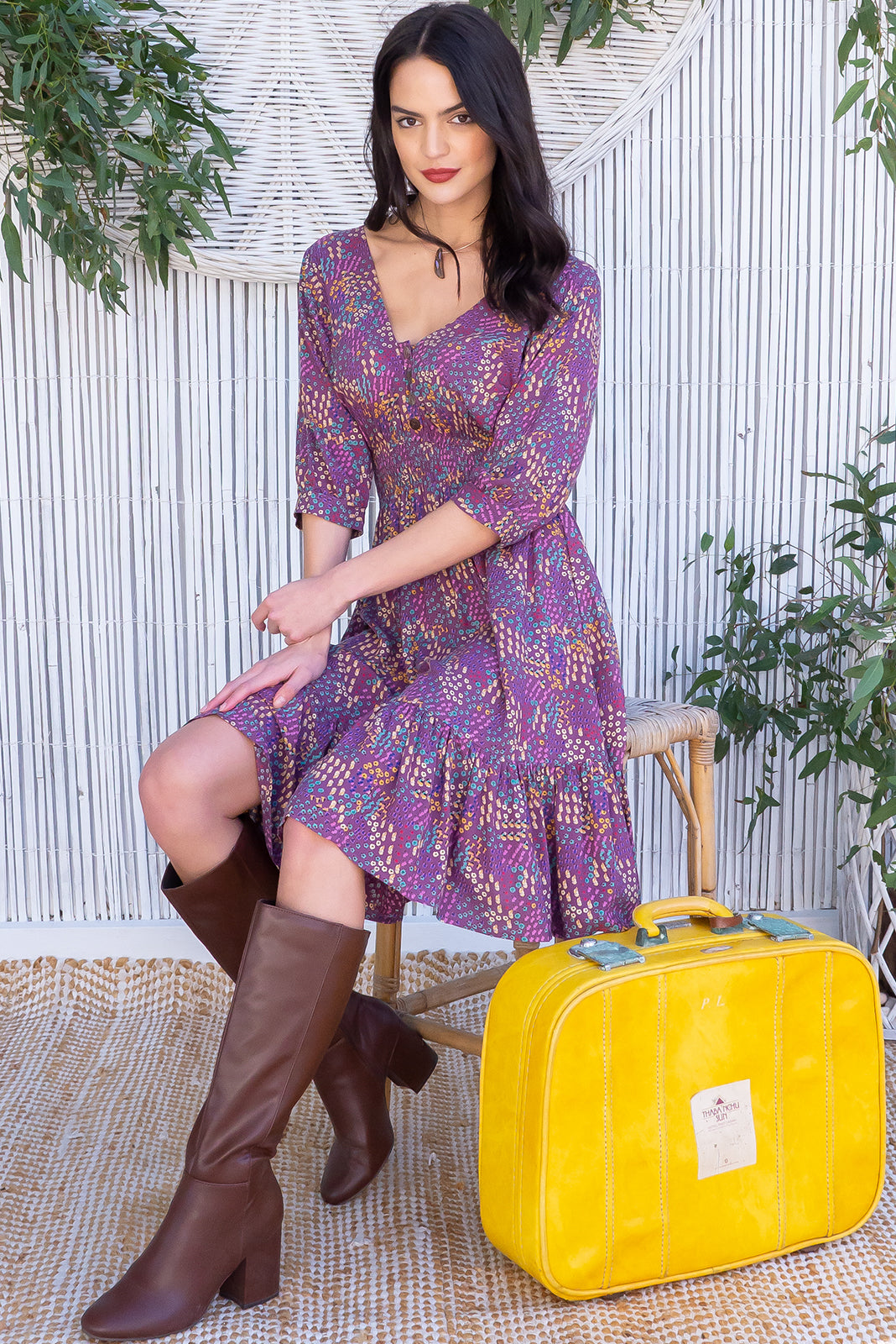 Sally La De Dah Lilac Dress, a pretty retro frock, featuring fnctional button down detailing to waist, elasticated waist, loose 1/2 length cuffed sleeves, deep frill around the hemline and woven 100% rayon in Dusty purple base with multicoloured flowers.