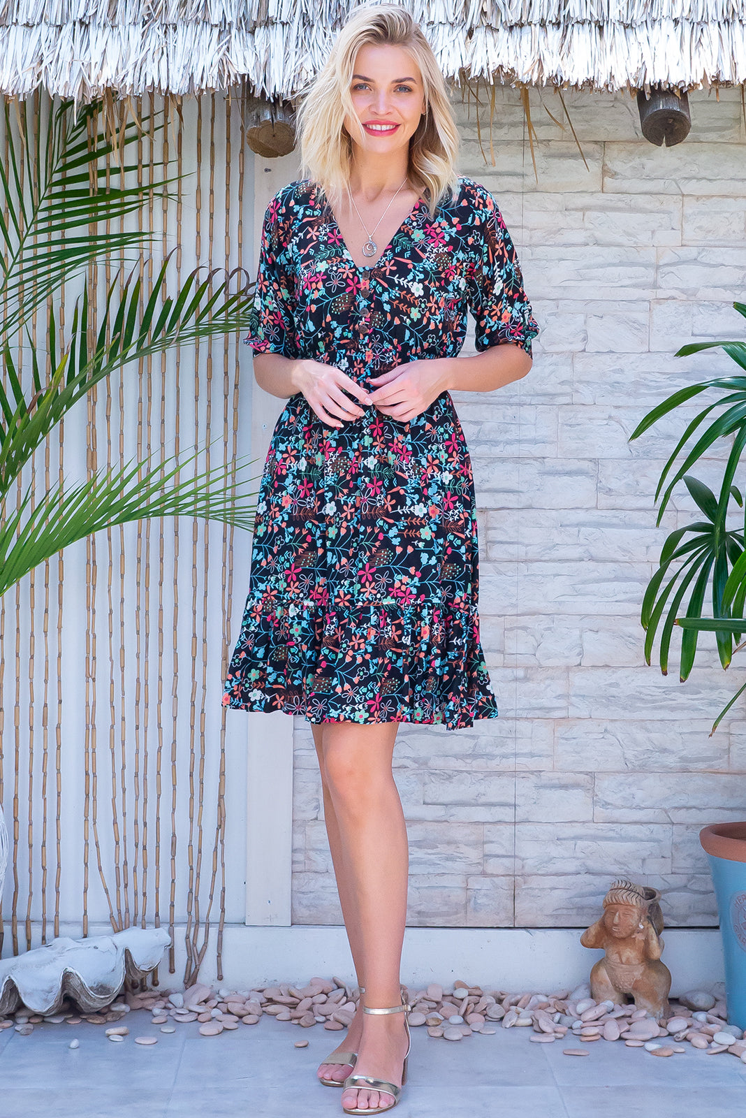 The Sally Noir Amusante Dress features lasticated waist, loose 1/2 length cuffed sleeves, side pockets, deep frill around the hemline and 100% rayon in black base with multicoloured floral print.