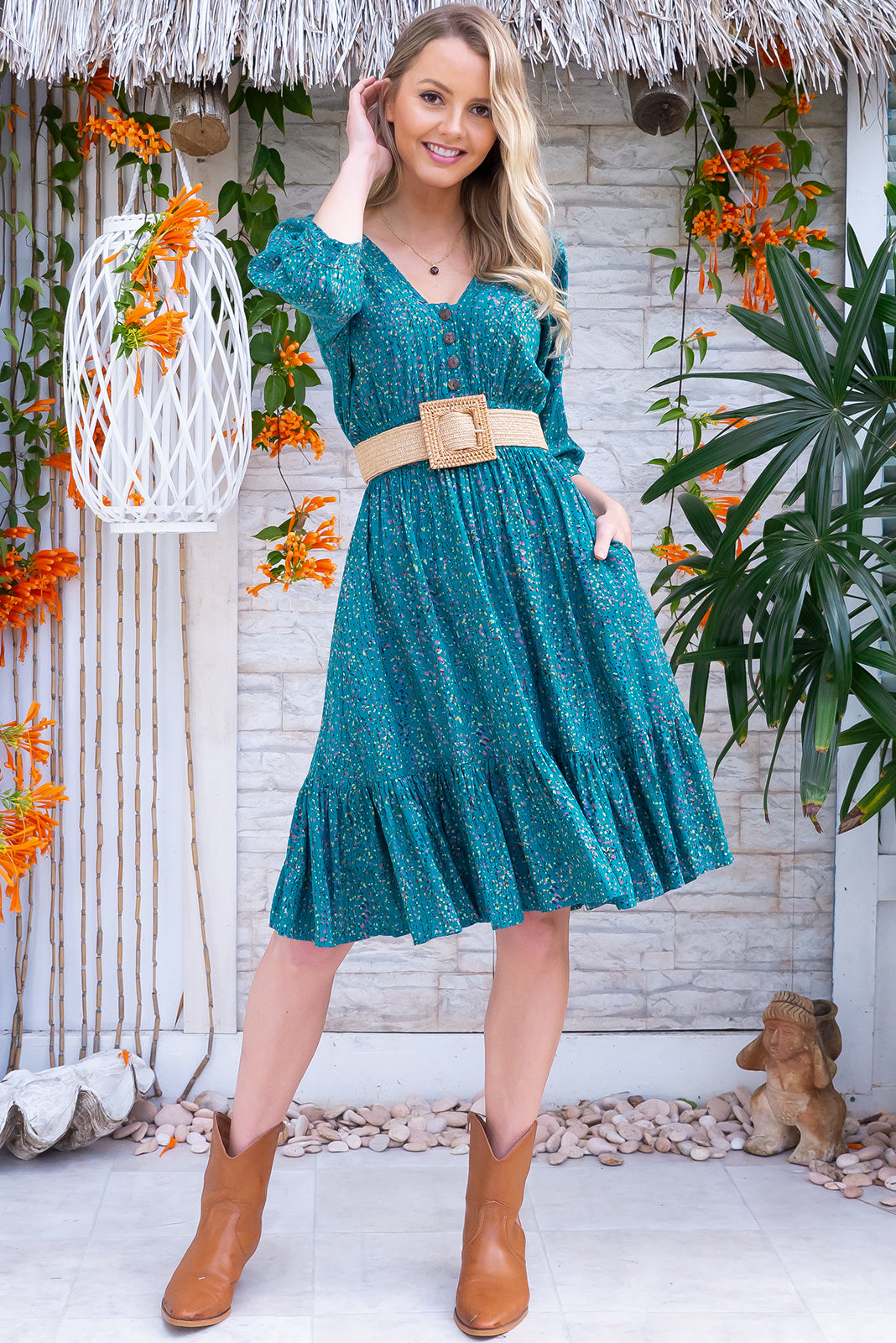 Sally Trellis Teal Mini Dress is a knee length dress featuring functional button down detailing to waist, loose 1/2 length cuffed sleeves and woven 100% rayon in pretty frilled hem. Teal base with petite water coloured vine print.