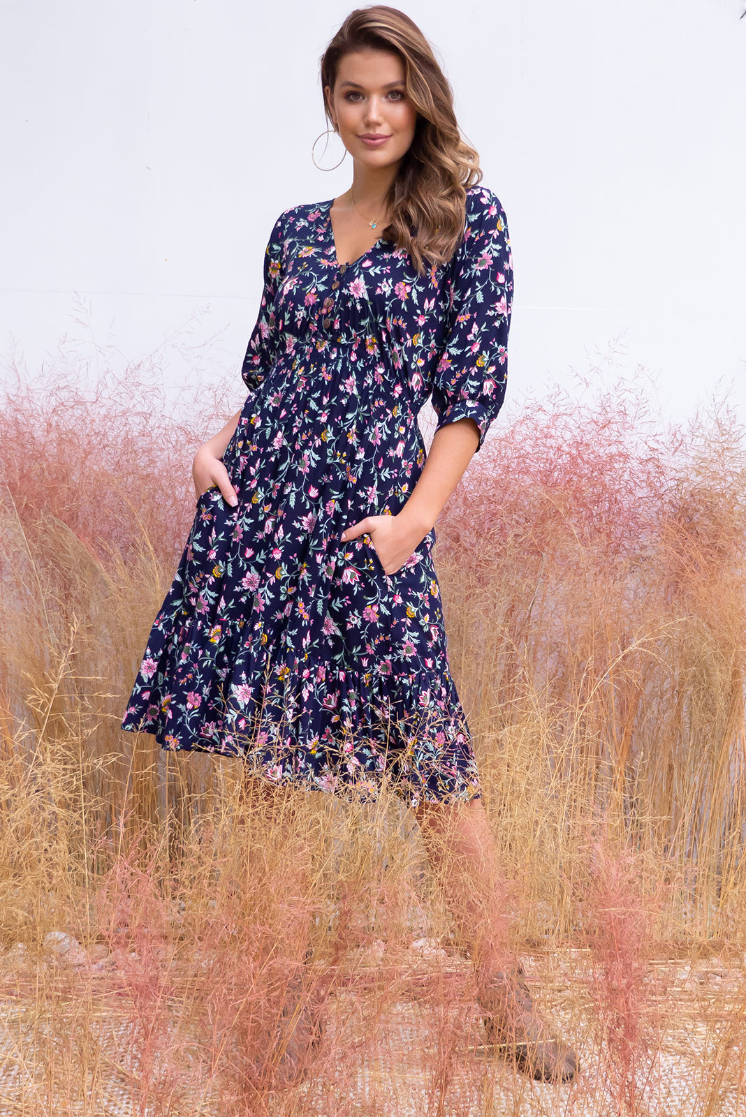 Sally Sugar Midnight dress features elasticated empire line with a cap sleeve, deep v neck and functional button front the fabric is a soft woven rayon in a dark inky navy enchanted bohemian floral print