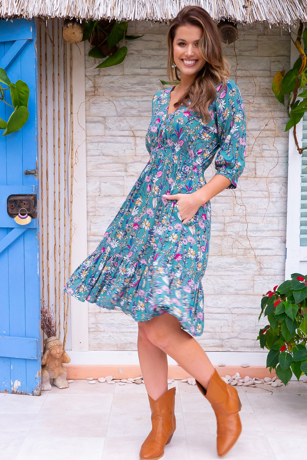 Sally Palma Green dress features elasticated empire line with a cap sleeve, deep v neck and functional button front the fabric is a soft woven rayon in a dark sea foam green floral print