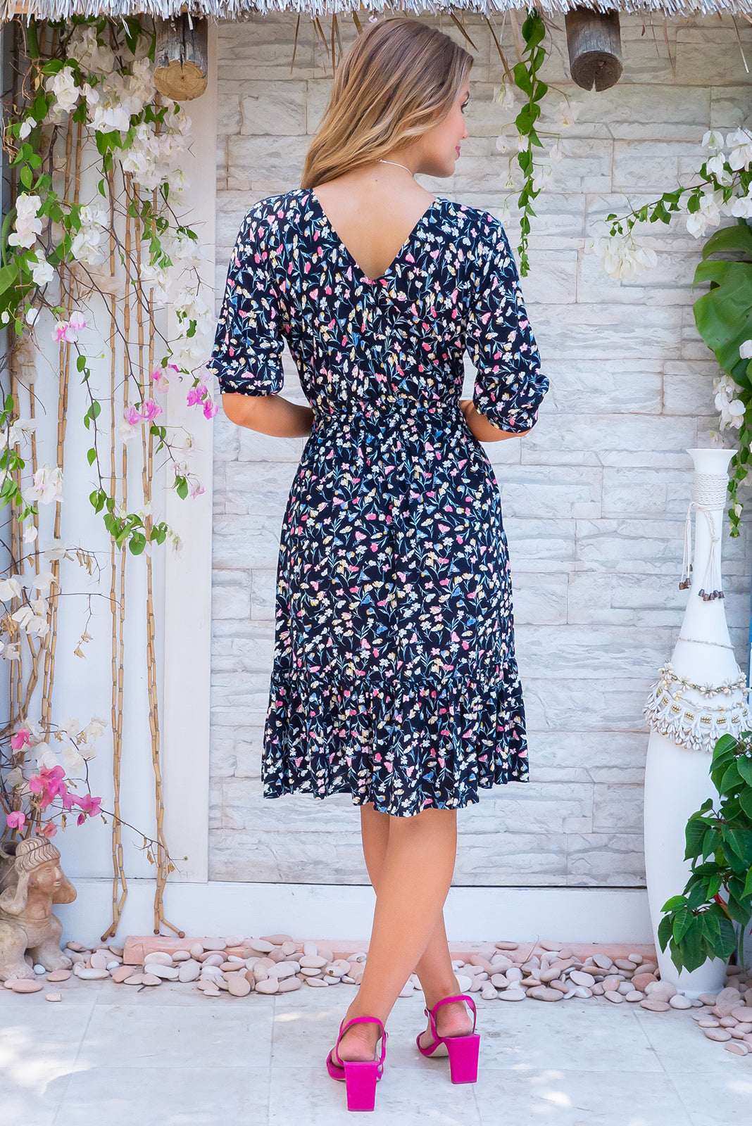 Sally Vinca Piana Noir Mini Dress, bohemian summer style, 100% rayon, knee length, functional button down detailing to waist, loose 1/112 length cuffed sleeves, deep frill around hemline, deep navy base with small magenta, gold and grey blue floral print.