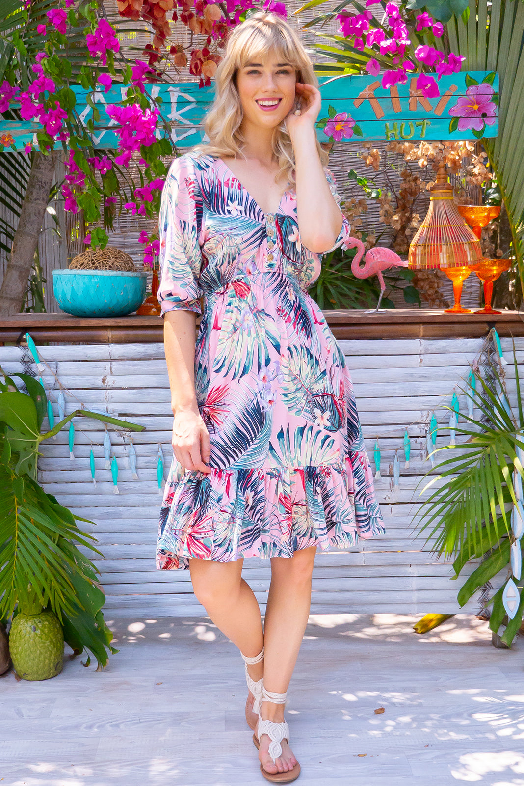 Sally Pink Palms Mini Dress, bohemian summer style, 100% rayon, functional button down to waist, loose 1/2 length cuffed sleeves, elasticated waist, three rows of soft shirring around the waist, frilled hemline, soft pink base with large red, forest green, mint and white floral and palm print.