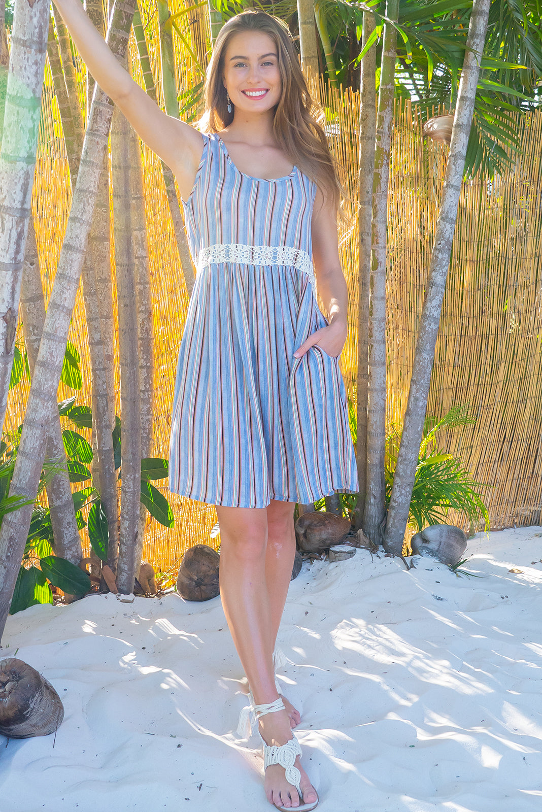 Sandi Beach Oceania Dress is a soft cut sleeveless dress with a adjustable button tab with feature cotton lace in a soft powder blue stripe printed crinkle textured woven rayon