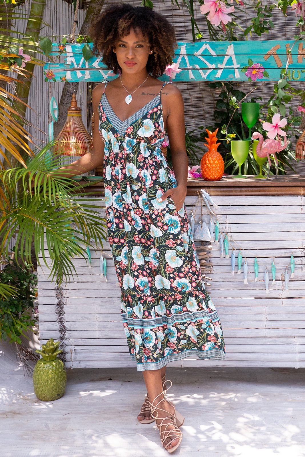 Sapphire Temptation Teal Maxi Dress for your next night on the town features woven 100% rayon, elasticated under bust, sleeveless with adjustable straps, V neckline, side pockets in black base with teal, white, magenta, blue and gold floral print with complimentary border print.