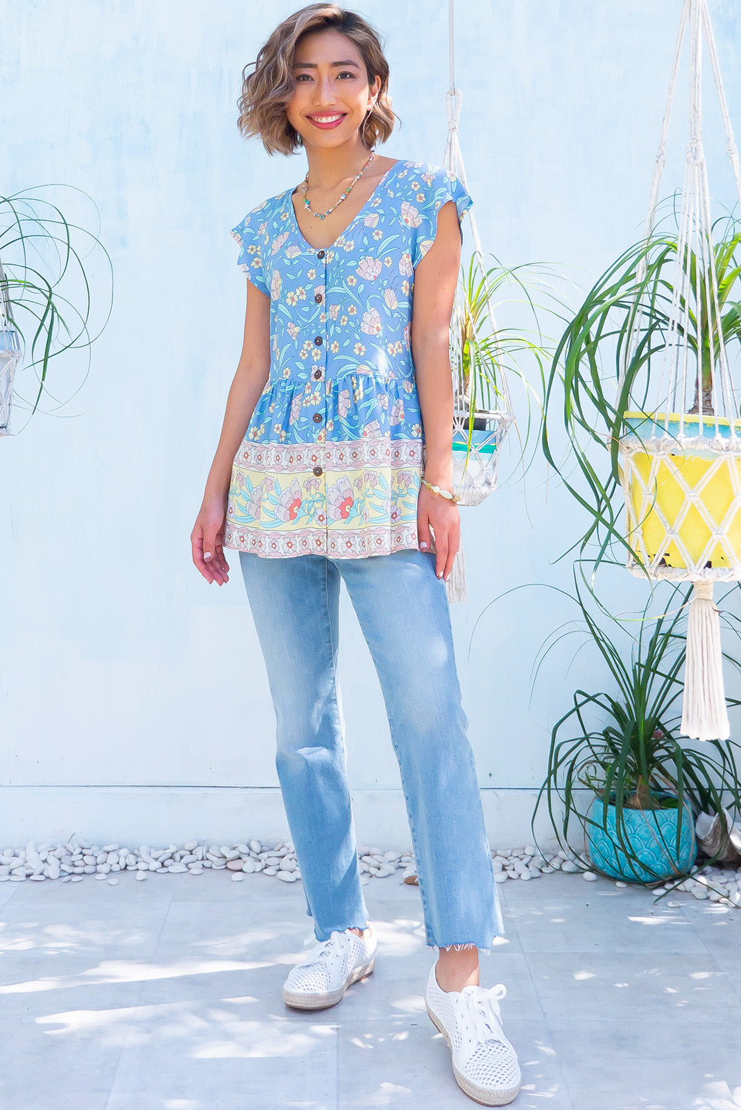 The Sea Coast Blouse Cornflower Blue features functional button front, scoop neckline, cap sleeves, soft peplum cut and 100% viscose in blue floral print with border feature.
