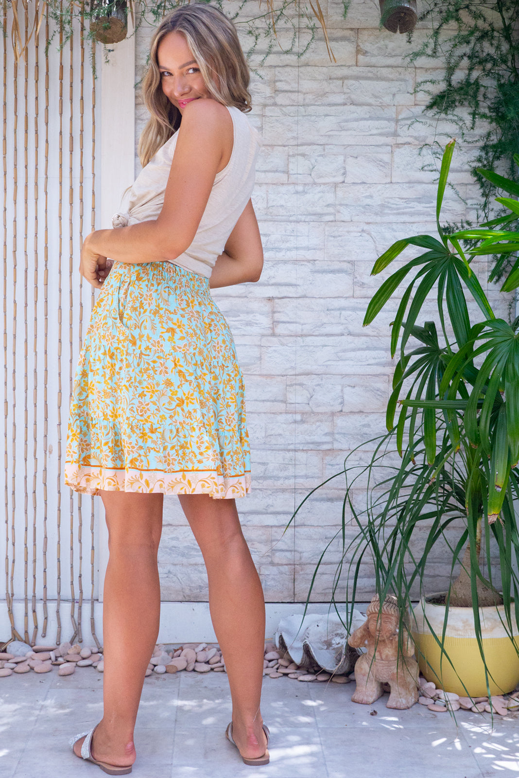 The Sea Coast Mini Skirt Seafoam features lightweight/non-stretch fabric, elasticated back waistband, tiered for flirty fullness, side pockets and woven 100% viscose in mint base with exotic golden print and soft peach border feature.