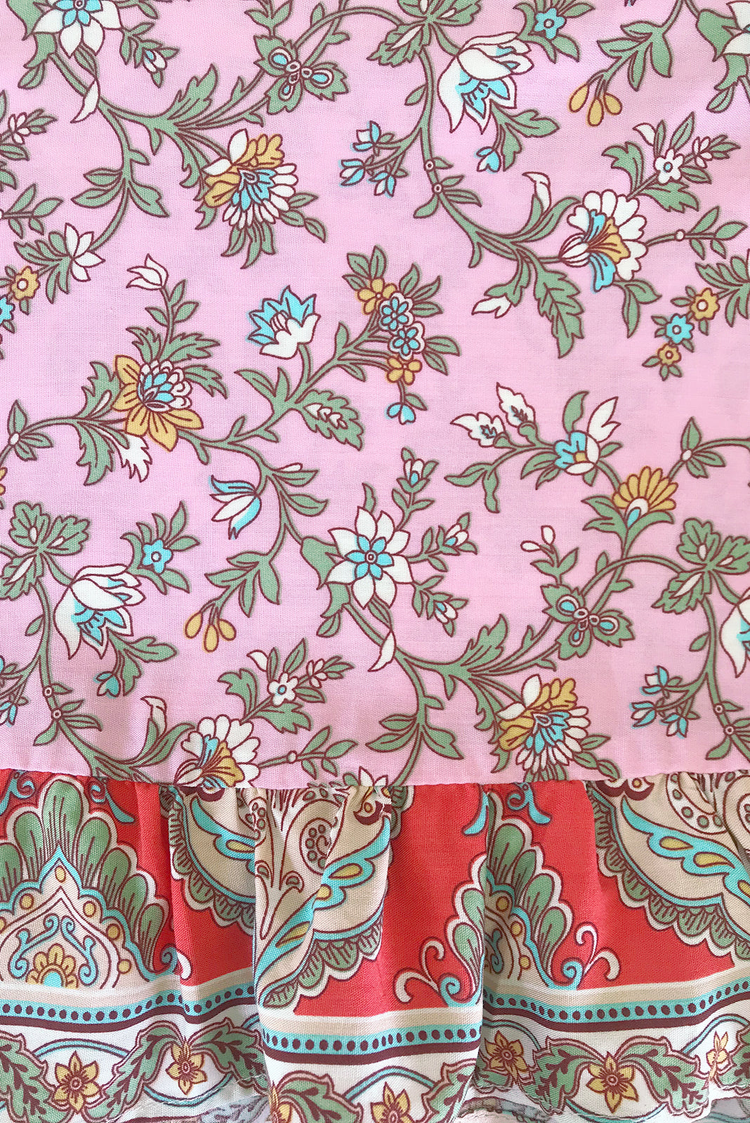 Fabric Swatch of Sea Coast Mini Skirt Strawberry Bohemian featuring 100% viscose in pale pink base with bohemian print and watermelon red border feature.
