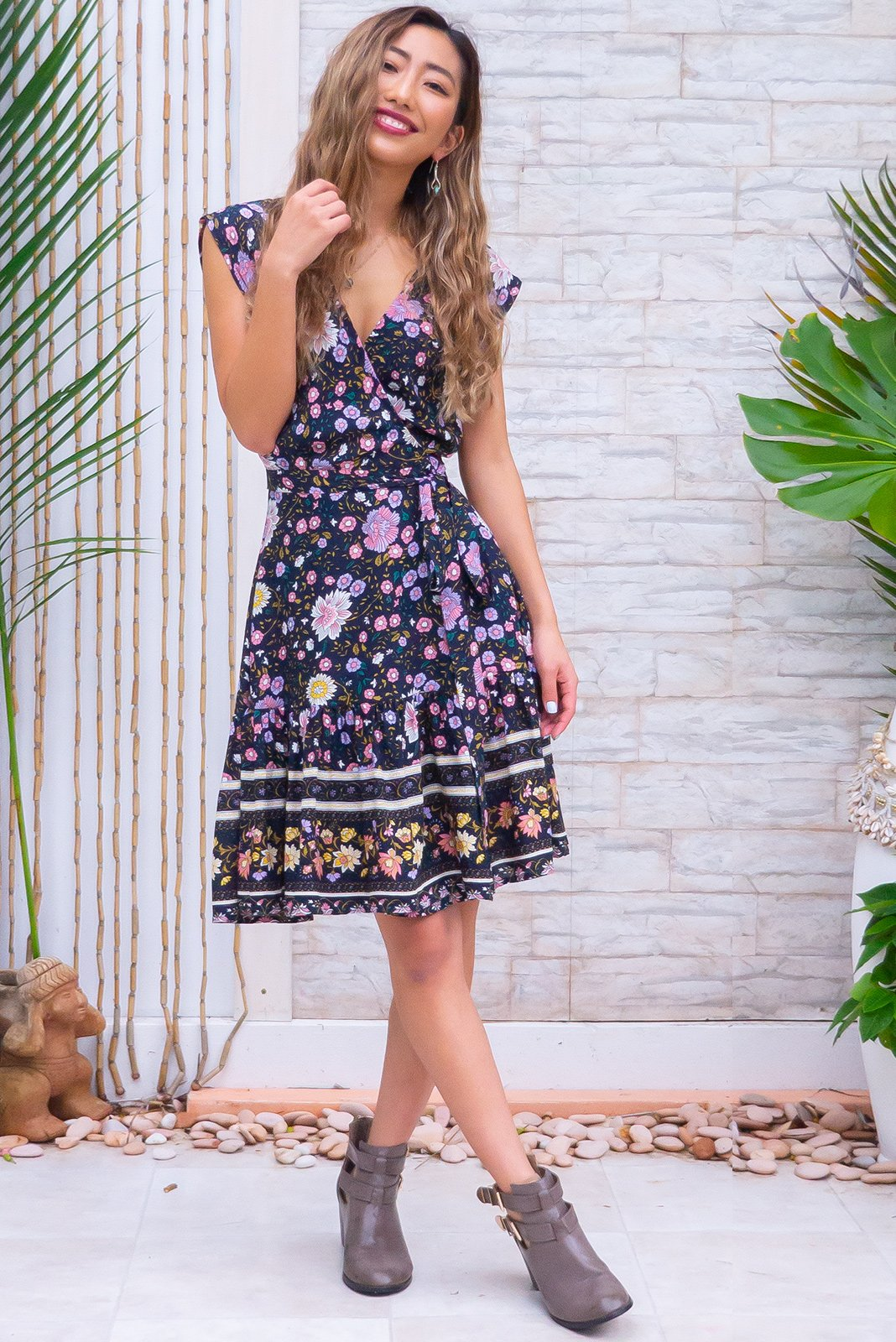 Sea Breeze Nantucket Ink Wrap Dress is a flirty frock having short sleeves with removable ties, flattering adjustable wrap design, elasticated waist band at the back, border print, frill hem, dark ink base with bohemian floral folk print in white, lavender, baby pink, yellow and greens in woven 100% rayon.