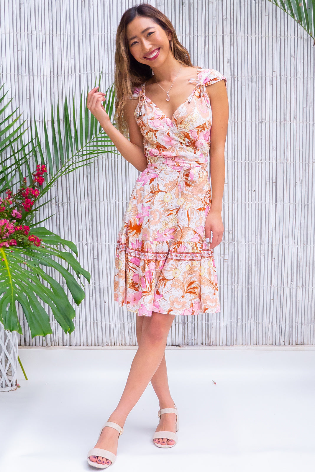 The vintage inspired dress, Sea Breeze Protea Pink Wrap Dress features short sleeves with removable ties, flattering adjustable wrap design, elasticated waist band at the back, frill hem with border print, cream base with summery floral folk print in pinks, amber, tan and pastel lemon in woven 100% rayon.