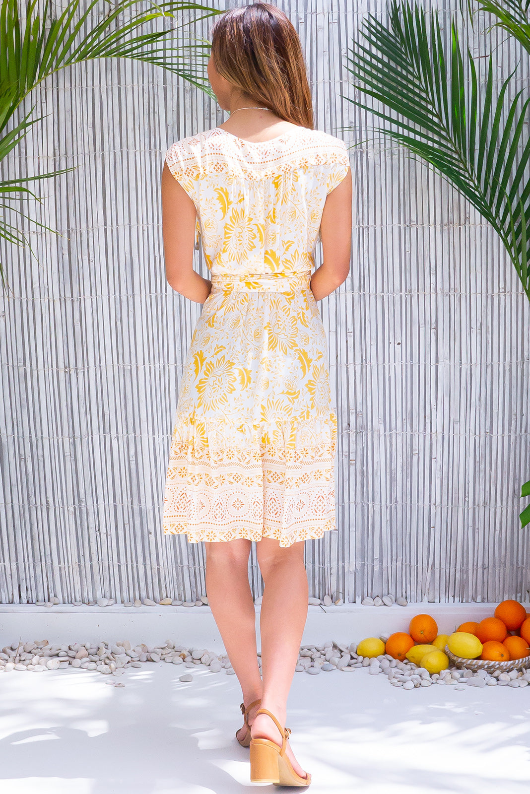 The Sea Breeze Riviera Gold Wrap Dress has short sleeves with removable ties, fattering adjustable wrap design, elasticated waist band at the back, border print, frill hem, crisp, white base with bohemian stencil print in yellow and amber in woven 100% rayon.