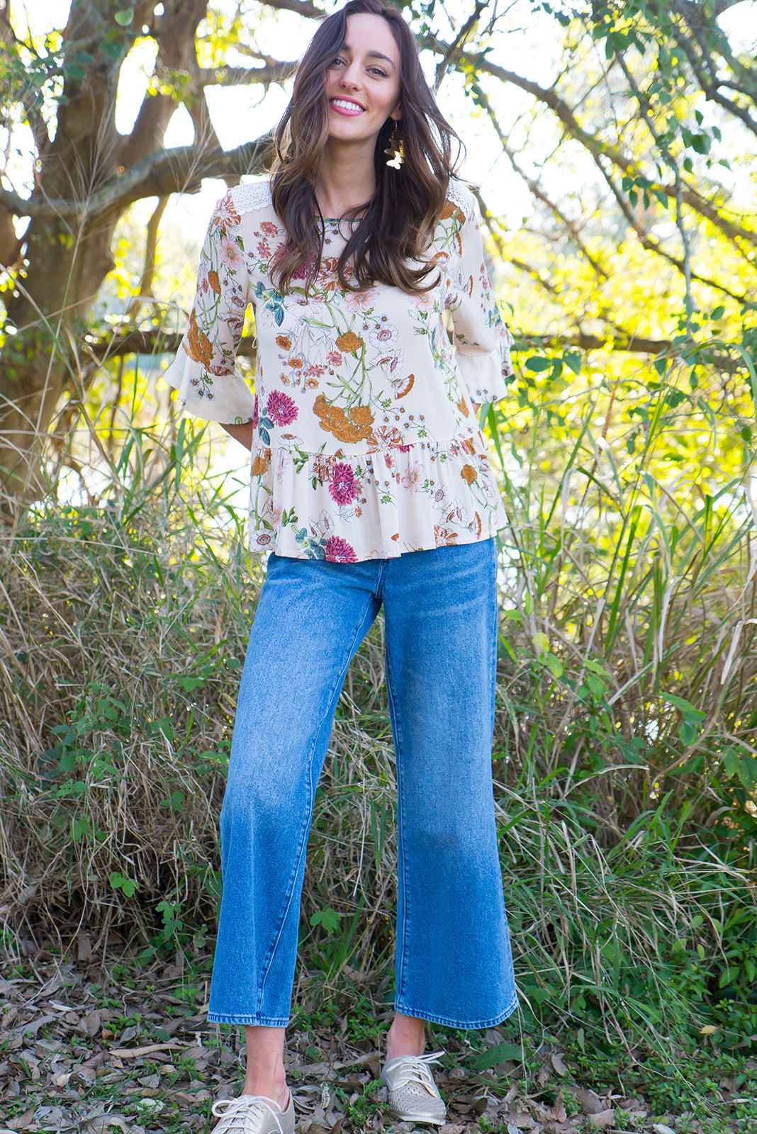 Siena Buttercup Top frill top has a soft drop waist and a bias cut frill sleeve cuff it comes in a crinkle textured rayon with a soft peach botanical print