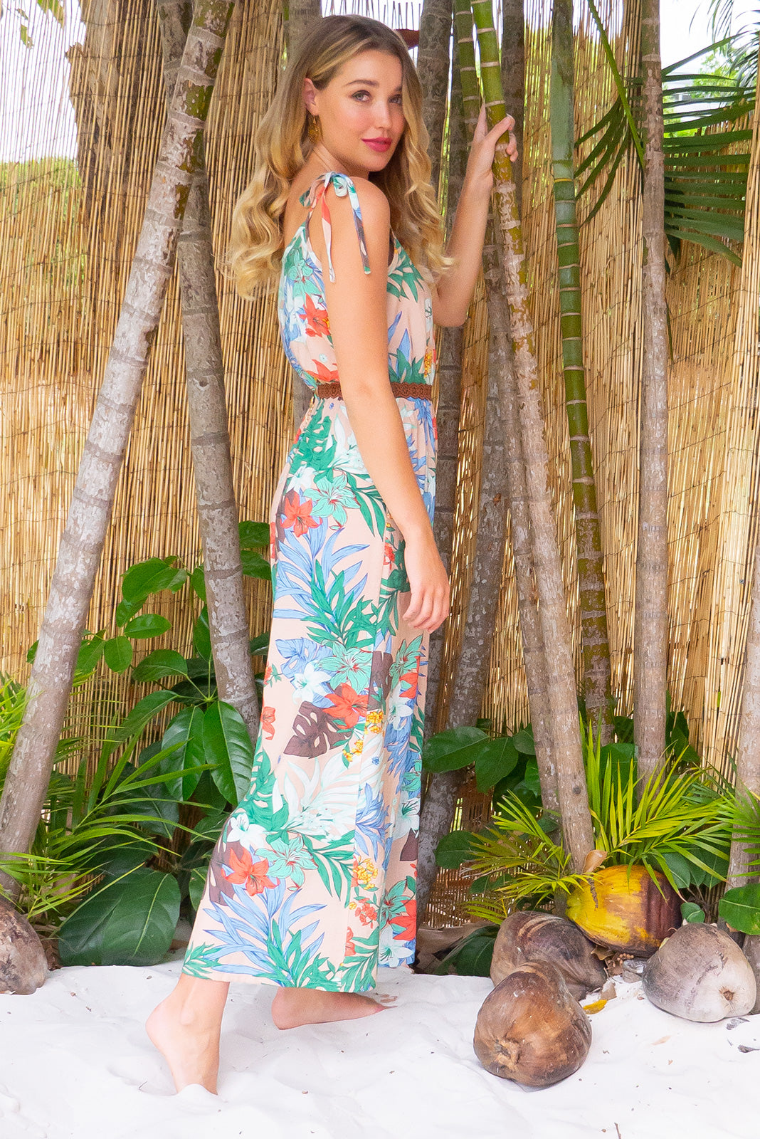 Sweet Caroline jumpsuit features deep side pockets, an elastic waist and adjustable strap in a cream based tropical print on a woven rayon nylon blend