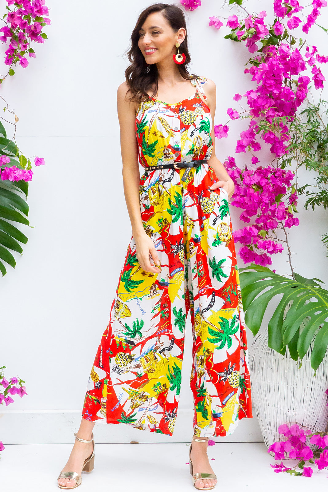 Sweet Caroline Postcard Red jumpsuit features deep side pockets, an elastic waist and adjustable strap in a red, white and yellow based tropical print on a woven rayon nylon blend