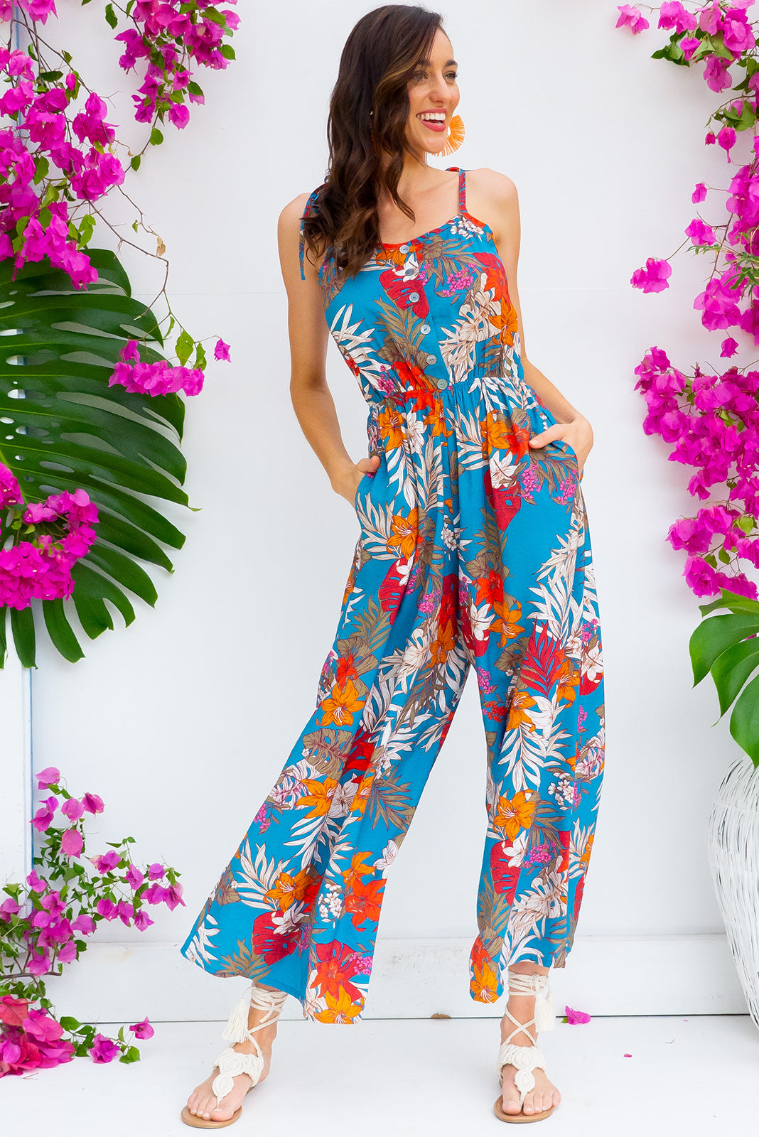 Sweet Caroline Teal Jungle jumpsuit features deep side pockets, an elastic waist and adjustable strap in a teal based tropical print on a woven rayon nylon blend