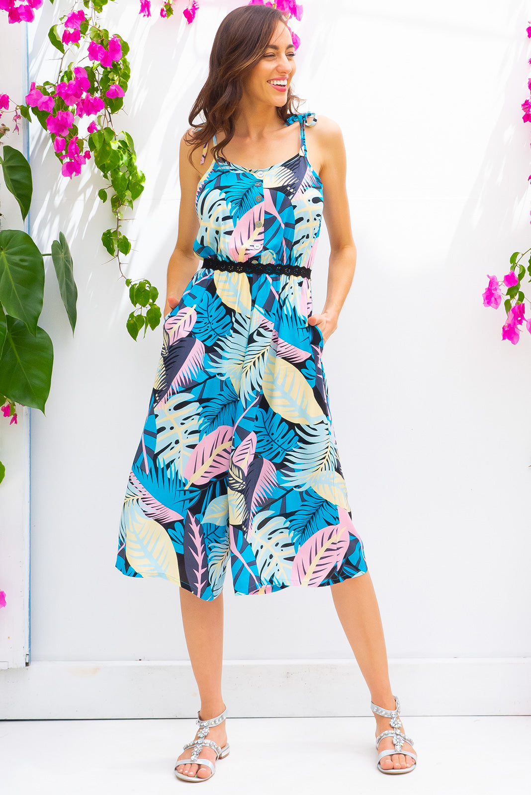 Sweet Pea Blue Style Midi jumpsuit features deep side pockets, an elastic waist and adjustable strap in a tropical print on a woven 100% rayon