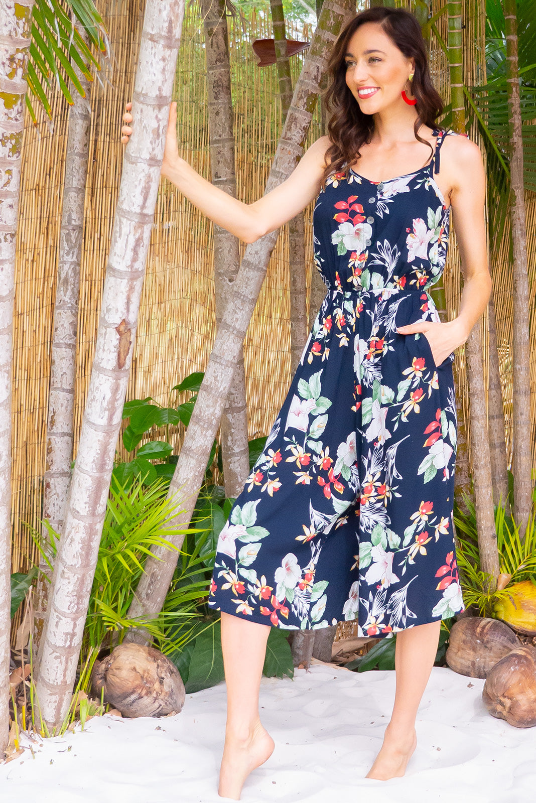 Sweet Pea Navy Chic Midi jumpsuit features deep side pockets, an elastic waist and adjustable strap in a dark navy floral print on a woven 100% rayon