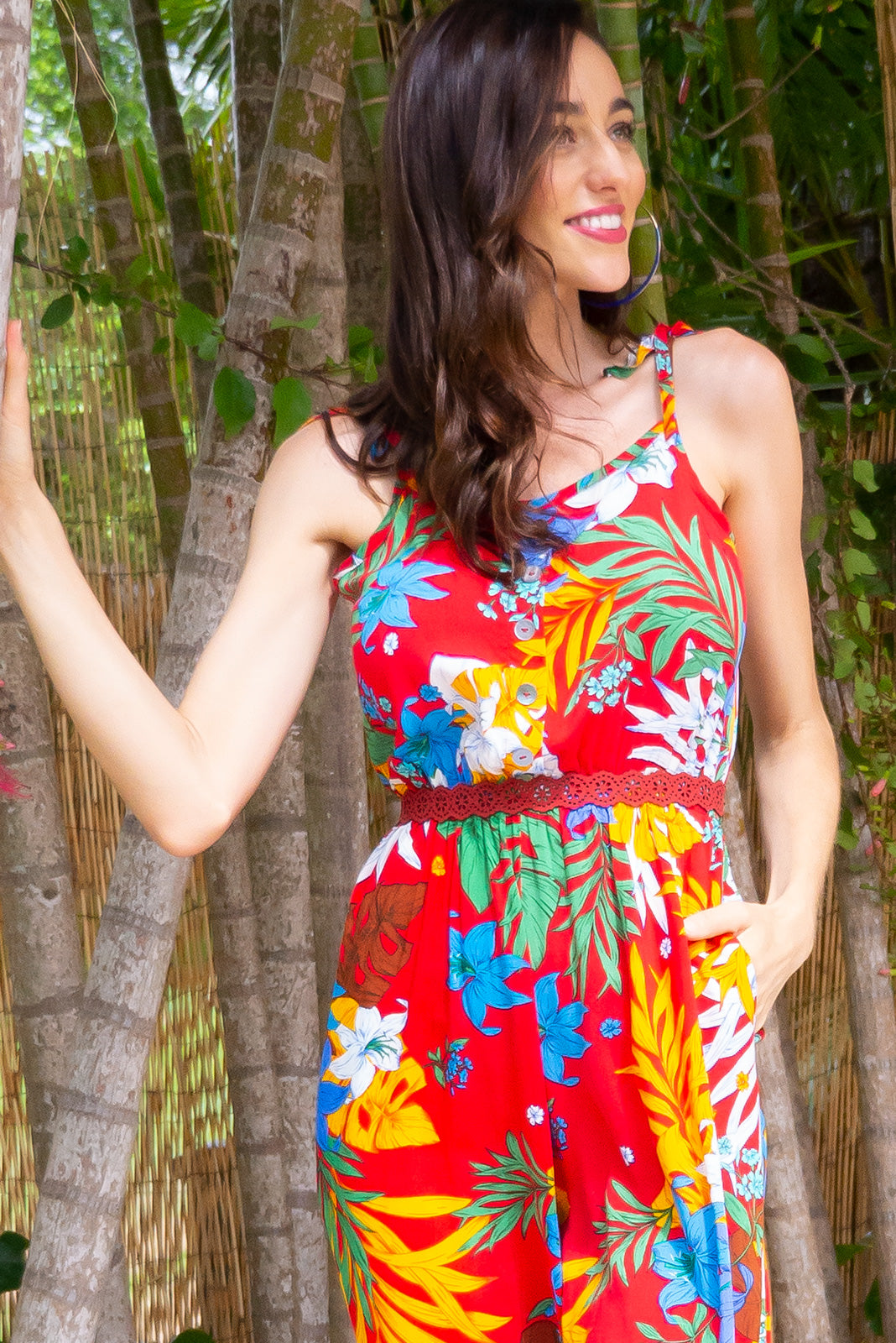 Sweet Pea Red Trend Midi jumpsuit features deep side pockets, an elastic waist and adjustable strap in a red based tropical print on a woven 100% rayon