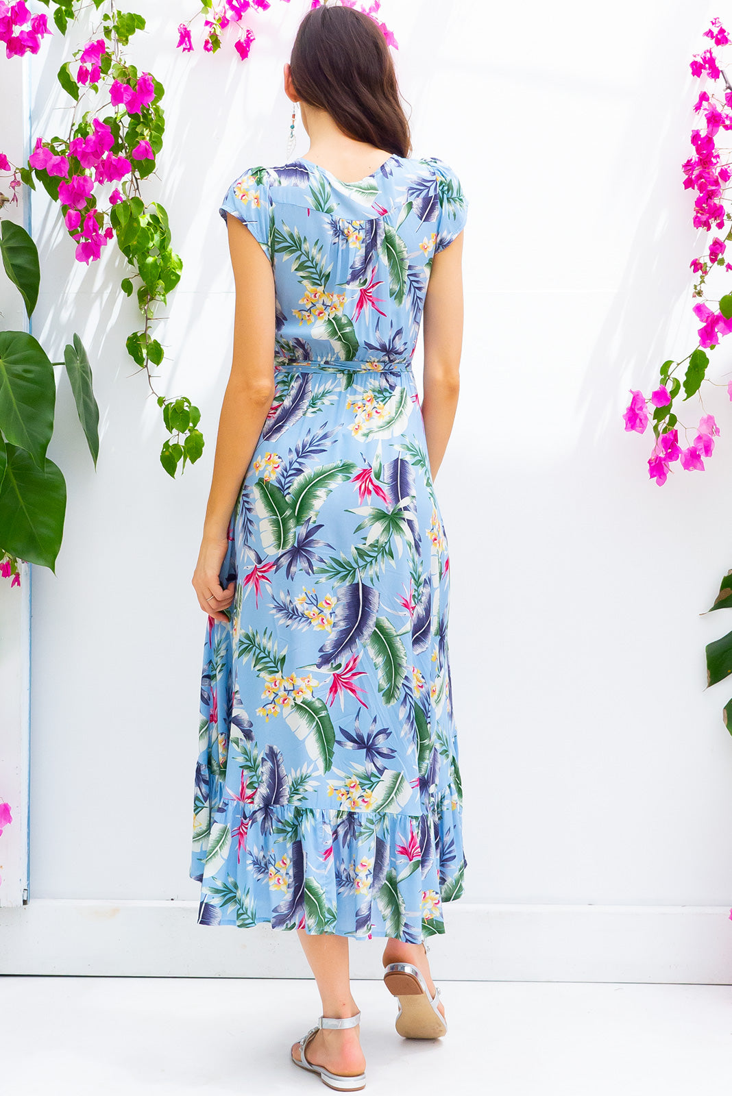 Symphony Tropical Skies Maxi Wrap Dress with a fitted bodice, cap sleeve and frill around the hem in a soft sky blue tropical floral print on soft rayon