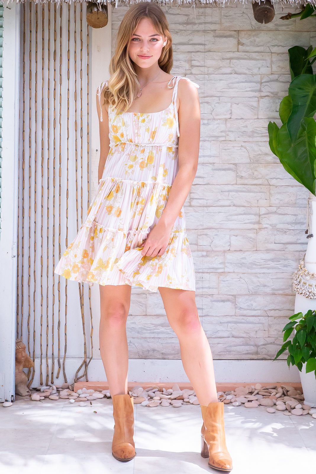 The Tea Stripes Mini Dress has adjustable tie up straps, babydoll cut, shirred elasticated upper back, tiered skirt, white base with muted pink stripe and 60's floral print in woven 100%  rayon.