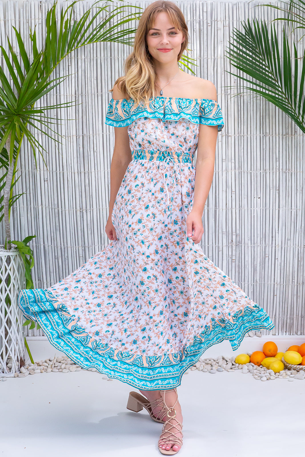 The an be worn on or off shoulders, elasticated drawstring waist, wlasticated frill neckline,frill hem with border print, white base with peach and turquoise print in woven 100% rayon.
