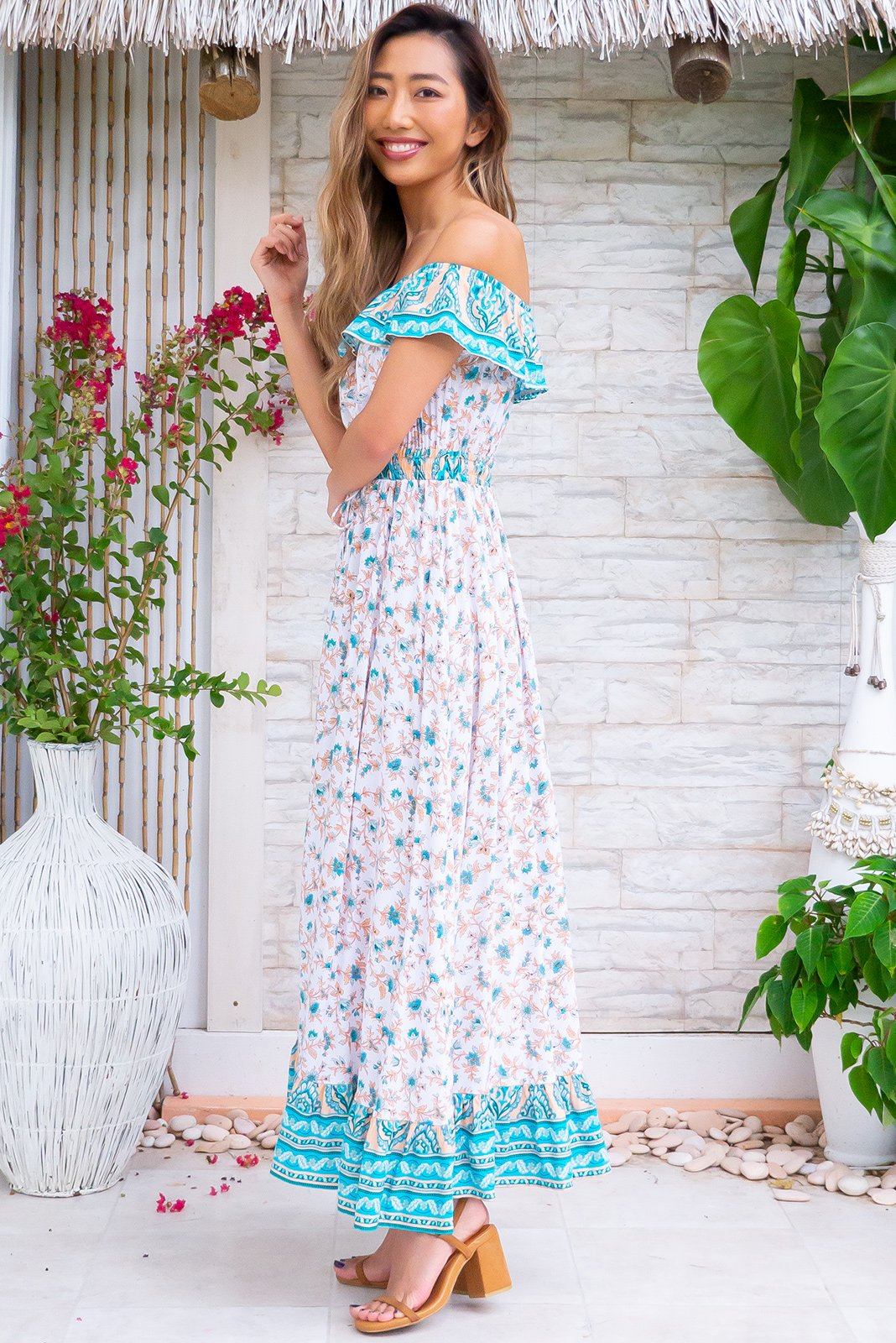 The Theoni Summer Maxi Dress, a perfect summer dress can be worn on or off shoulders, elasticated drawstring waist, elasticated frill neckline, frill hem with border print, white base with peach and turquoise print in woven 100% rayon.