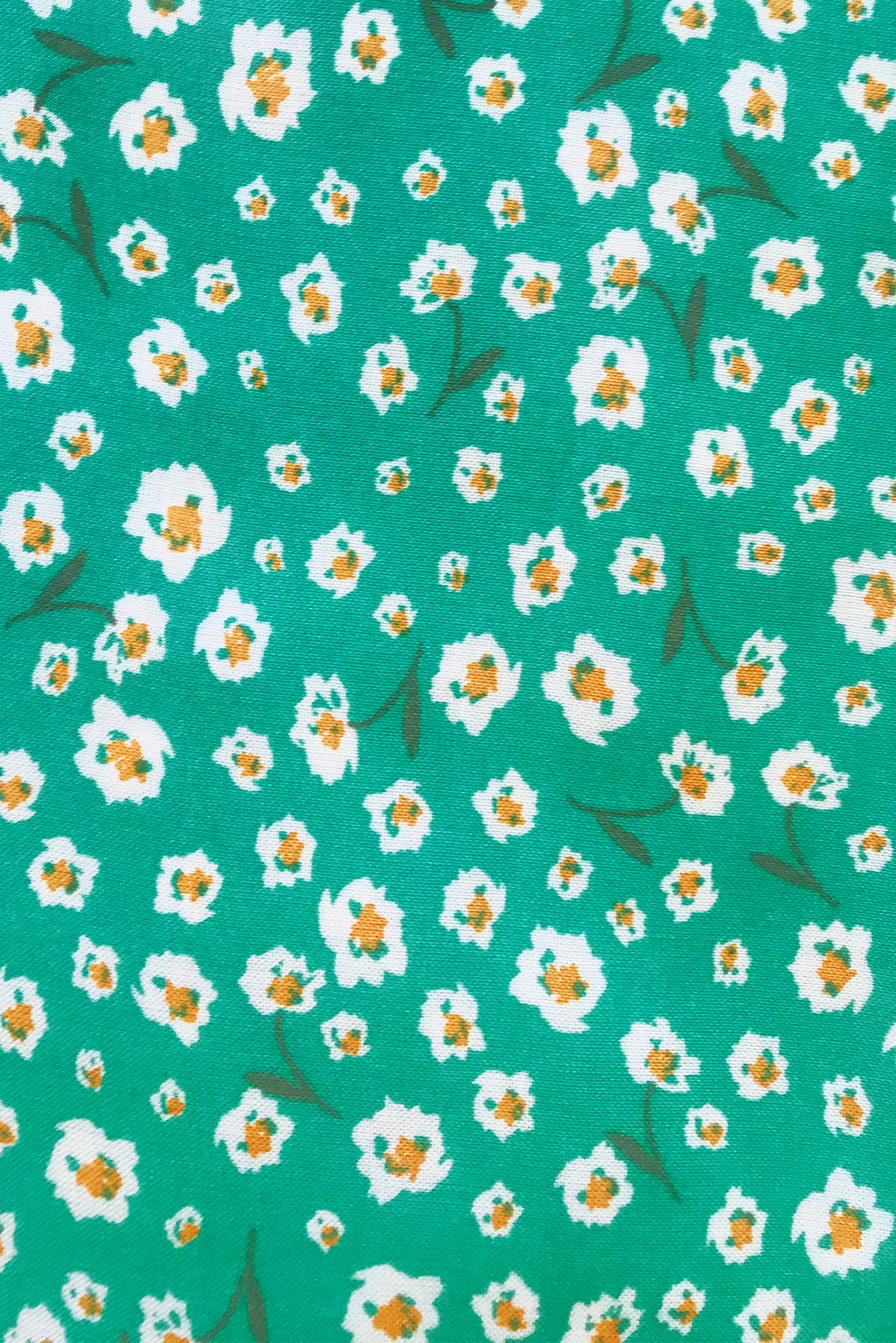 Fabric swatch ofTori Emerald Maxi Dress features emerald base with white ditzy floral print in woven 100% rayon.