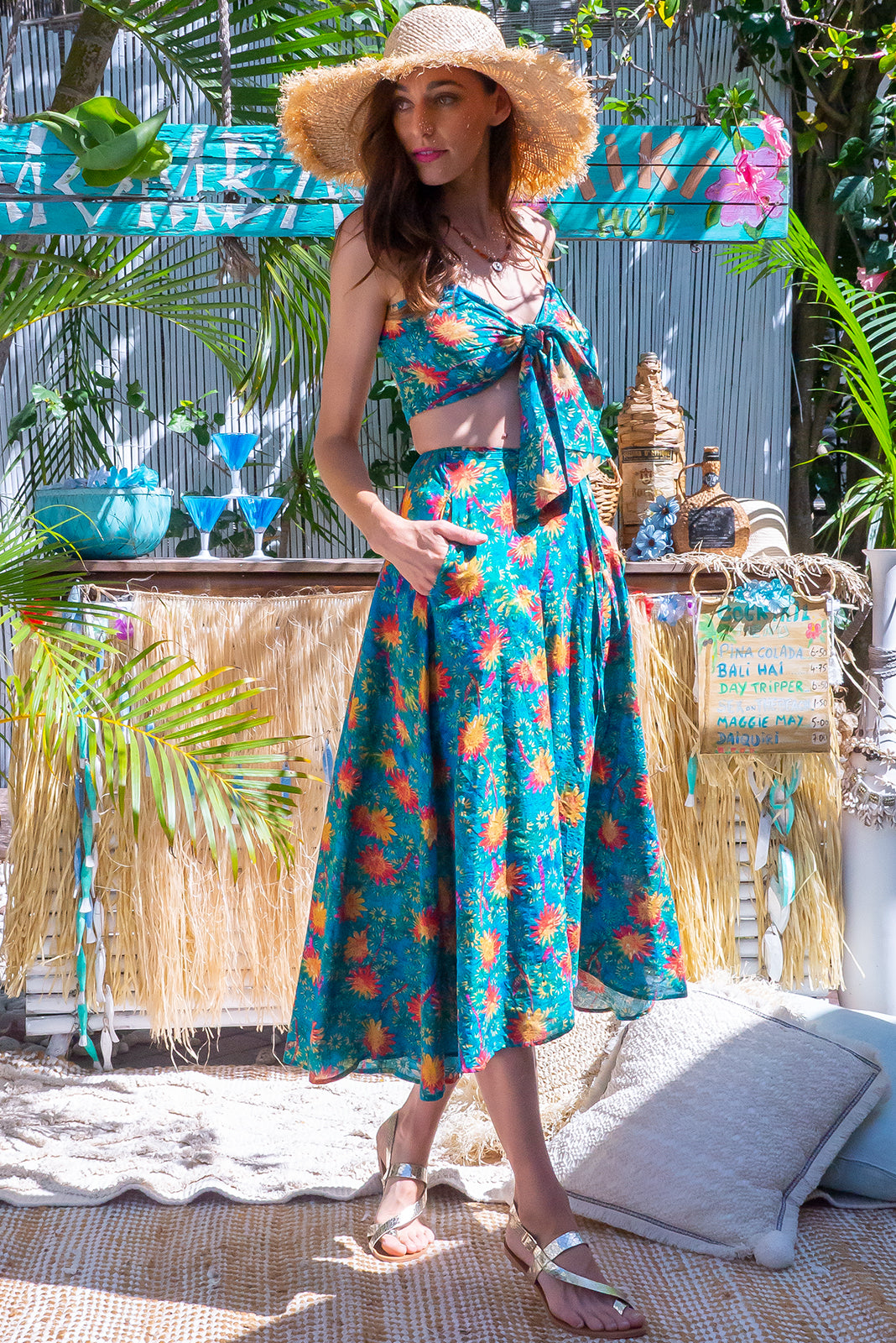 The Toucana Teal Sunshine Warp Skirt is functional wrap around design featuring elasticated back of waist, side pockets and 60% cotton, 40% viscose in retro, abstract flower print on teal wash effect base.