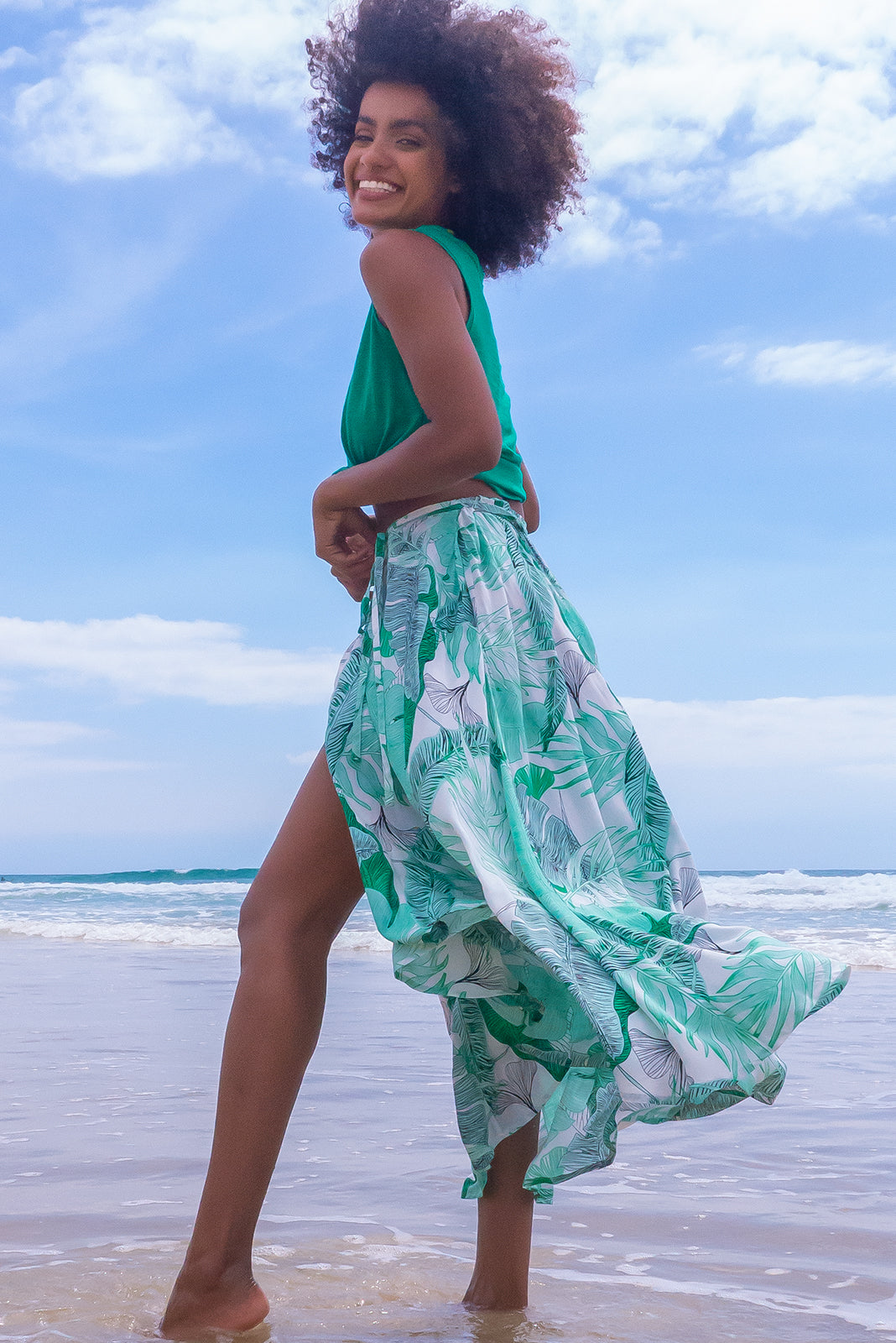 The Toucana Whispering Palms Wrap Skirt is a functional wrap around design featuring tie waist, high/low hemline, elasticated back of waist, side pockets and 100% viscose in large leaf print on white base.
