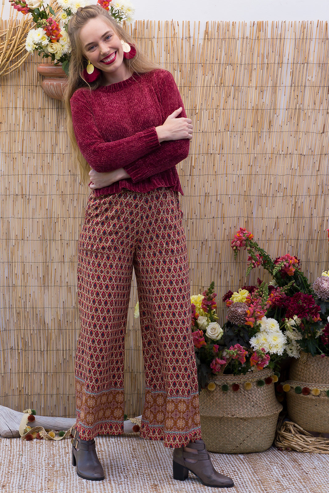 Traveller pants desert rust are wide leg pants with an elastic waist, deep pockets and they feature a boho inspired border print on a rust coloured woven rayon