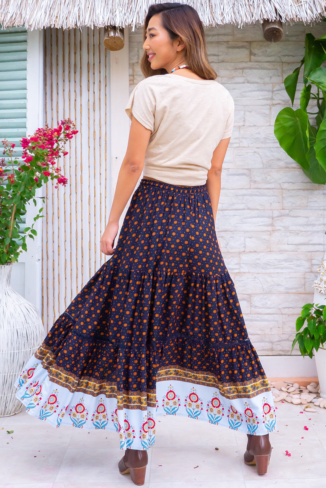 Trina Celestial Ink Maxi Skirt has elasticated, drawstring waistband, tiered skirt with lace insert, border print hem, ink base with golden suns and colourful folk border print in woven 100% rayon.